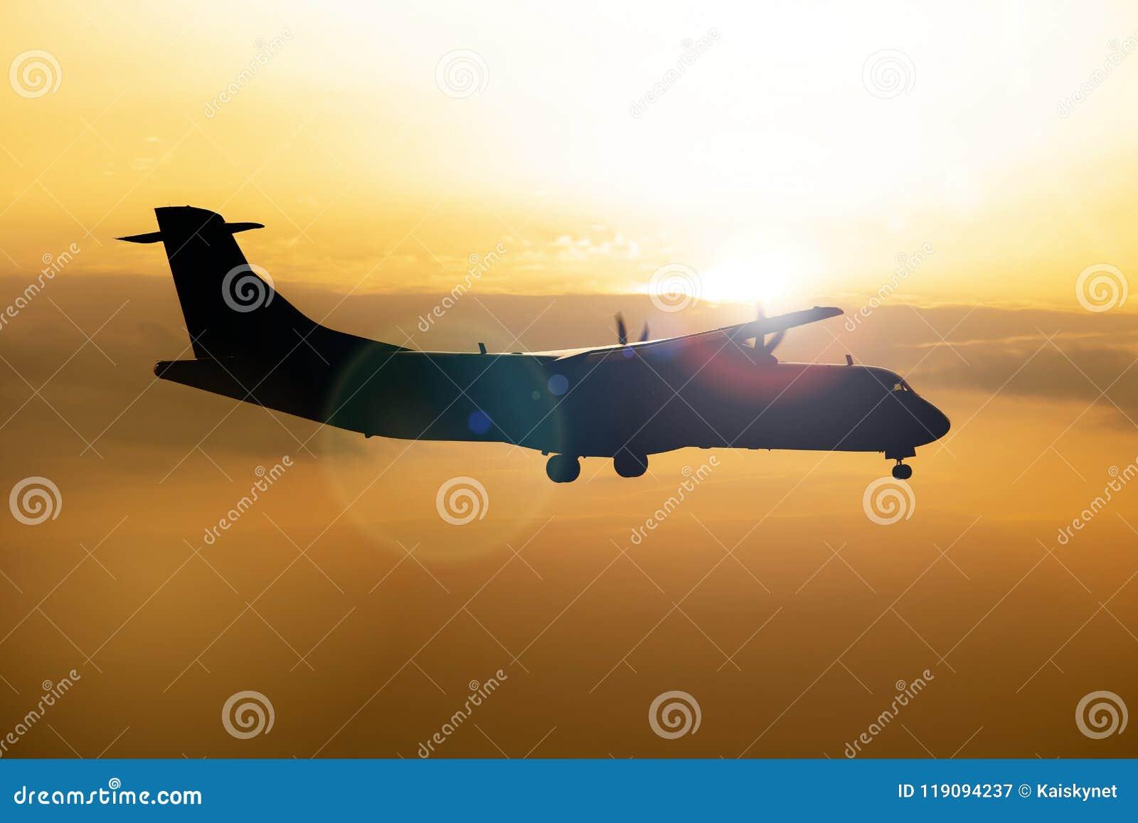 飞机剪影在五颜六色的剧烈的天空的在日落