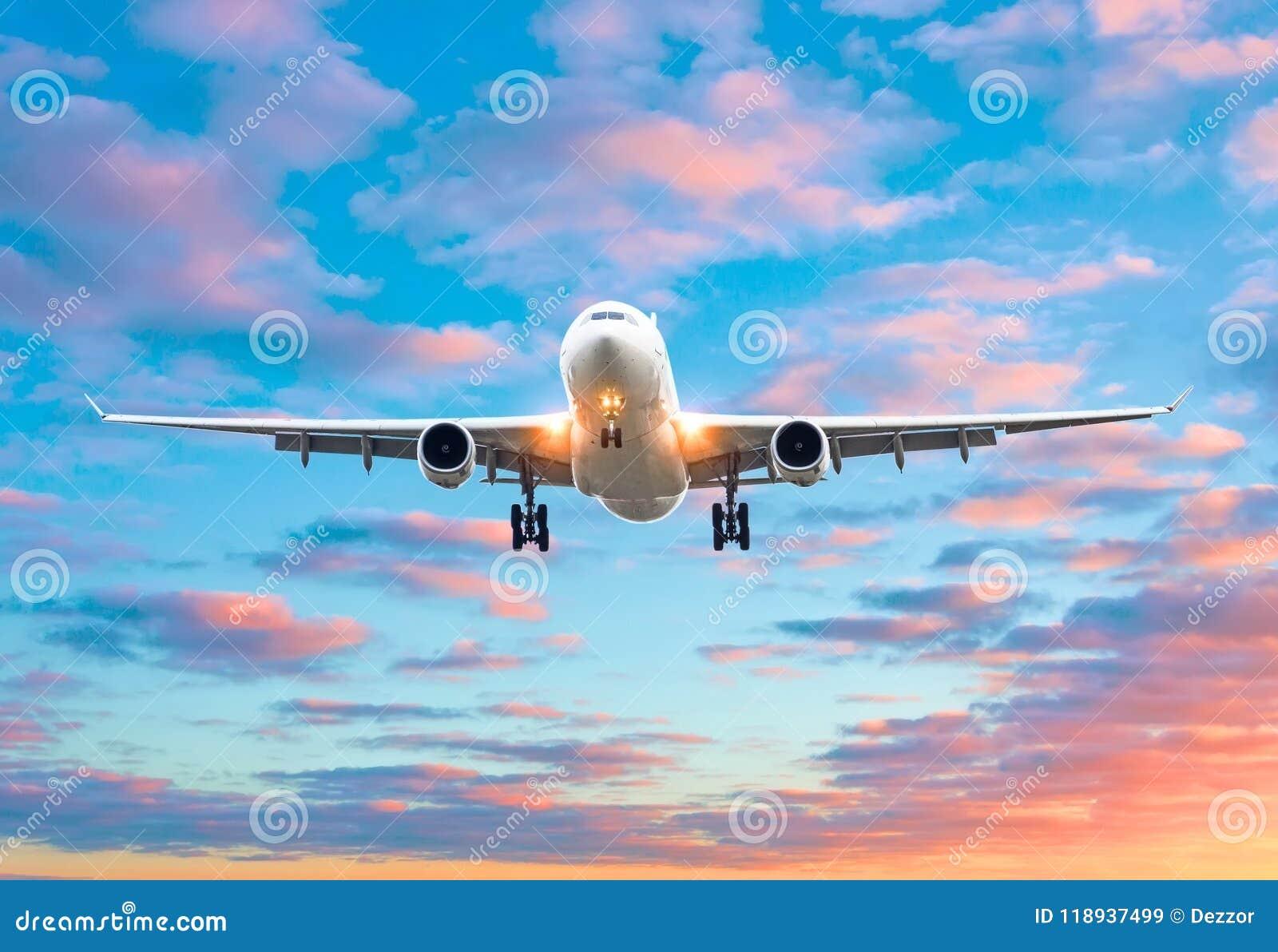 飞机飞行在一个跑道机场的到来着陆在一明亮的红色日落cloudscape期间的晚上