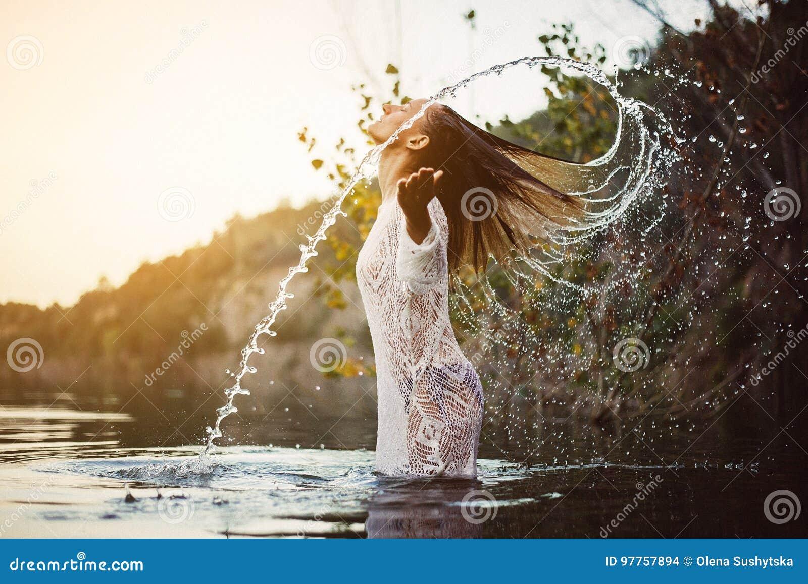 飞溅水的秀丽式样女孩与她的头发 青少年的女孩游泳和飞溅在夏天海滩