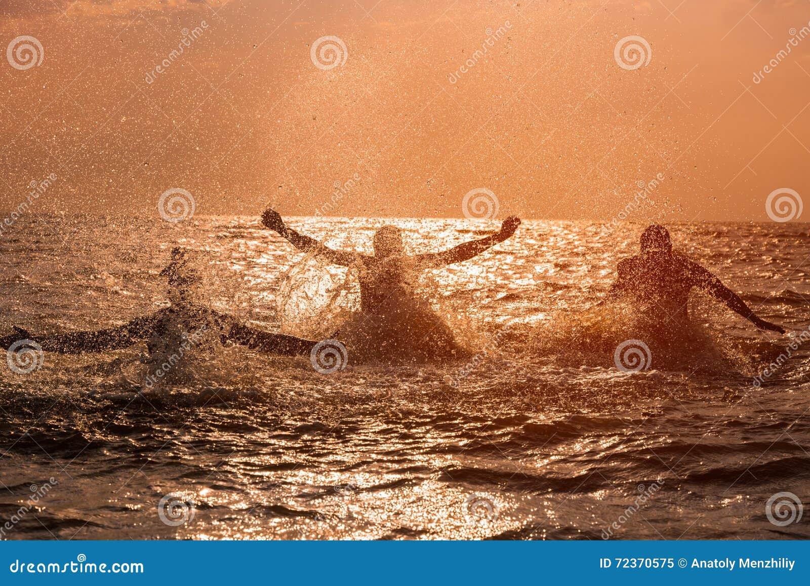 飞溅水的朋友在海在日落