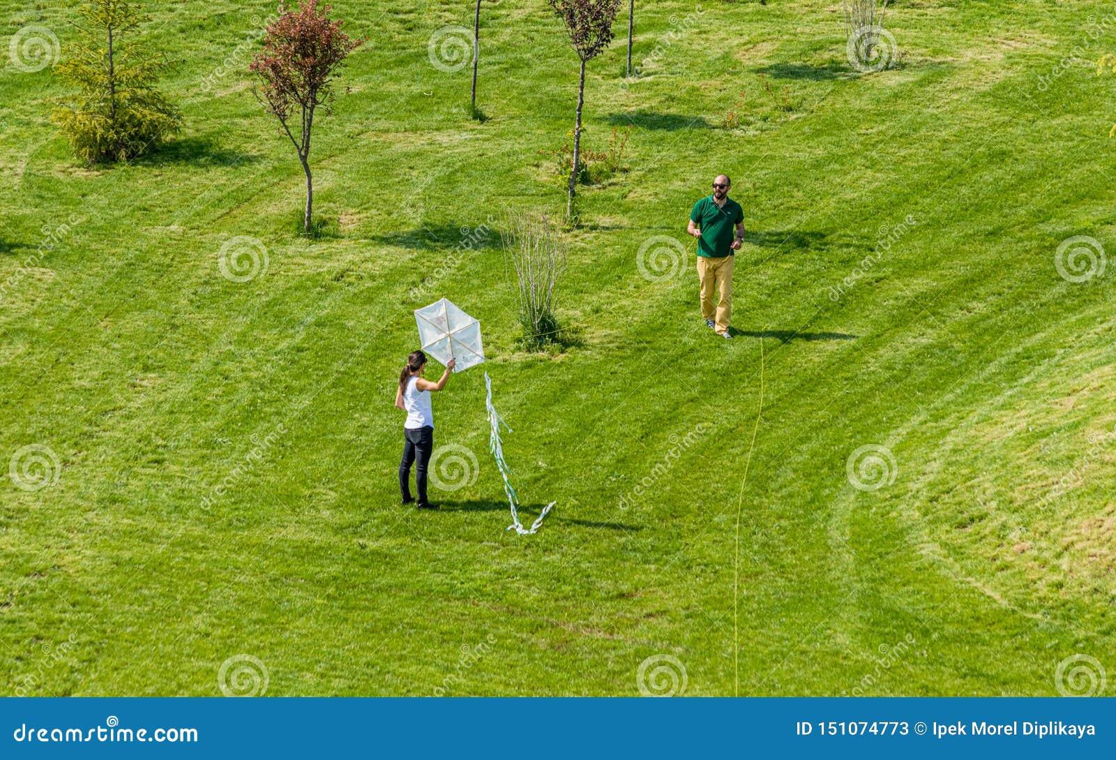 飞行一只白色风筝的男人和妇女在公园
