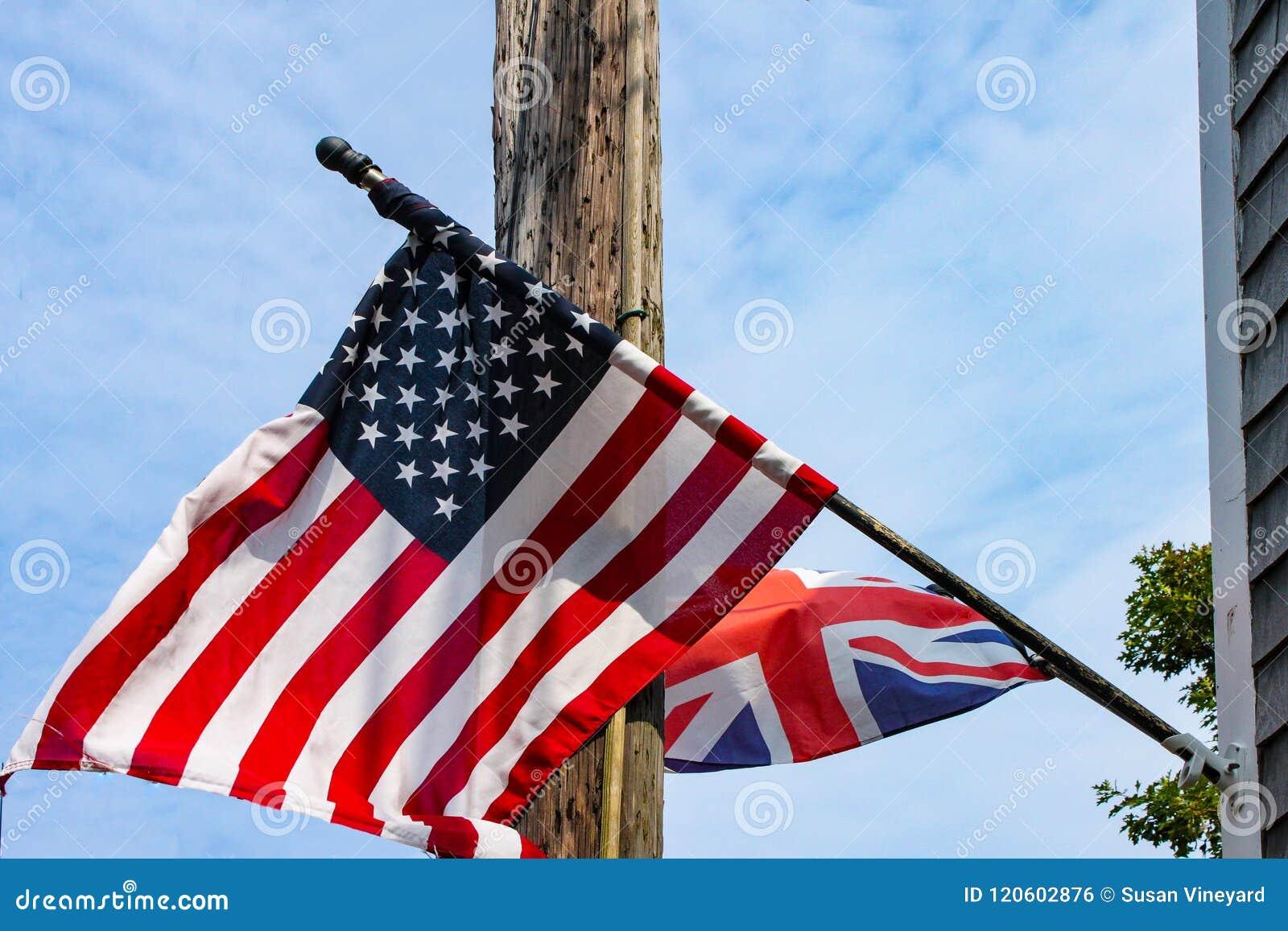 飞行从在一根电杆和蓝色多云天空前面的一个被风化的墙板房子的英国和美国国旗