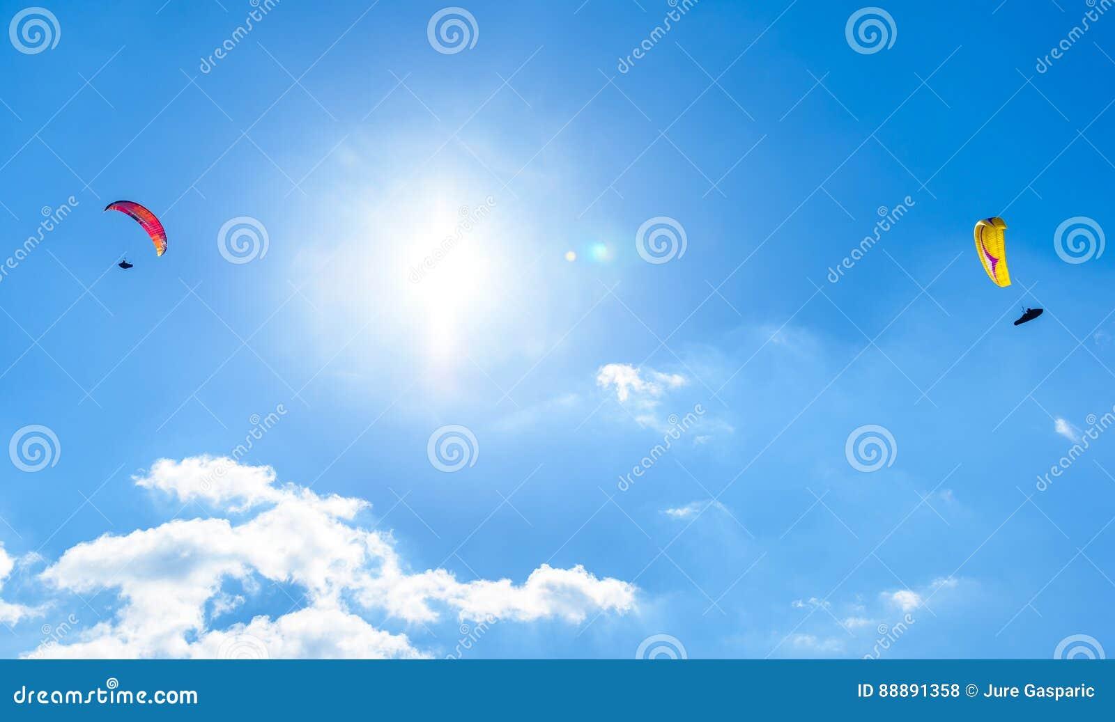飞行反对与白色云彩的蓝天的两个滑翔伞