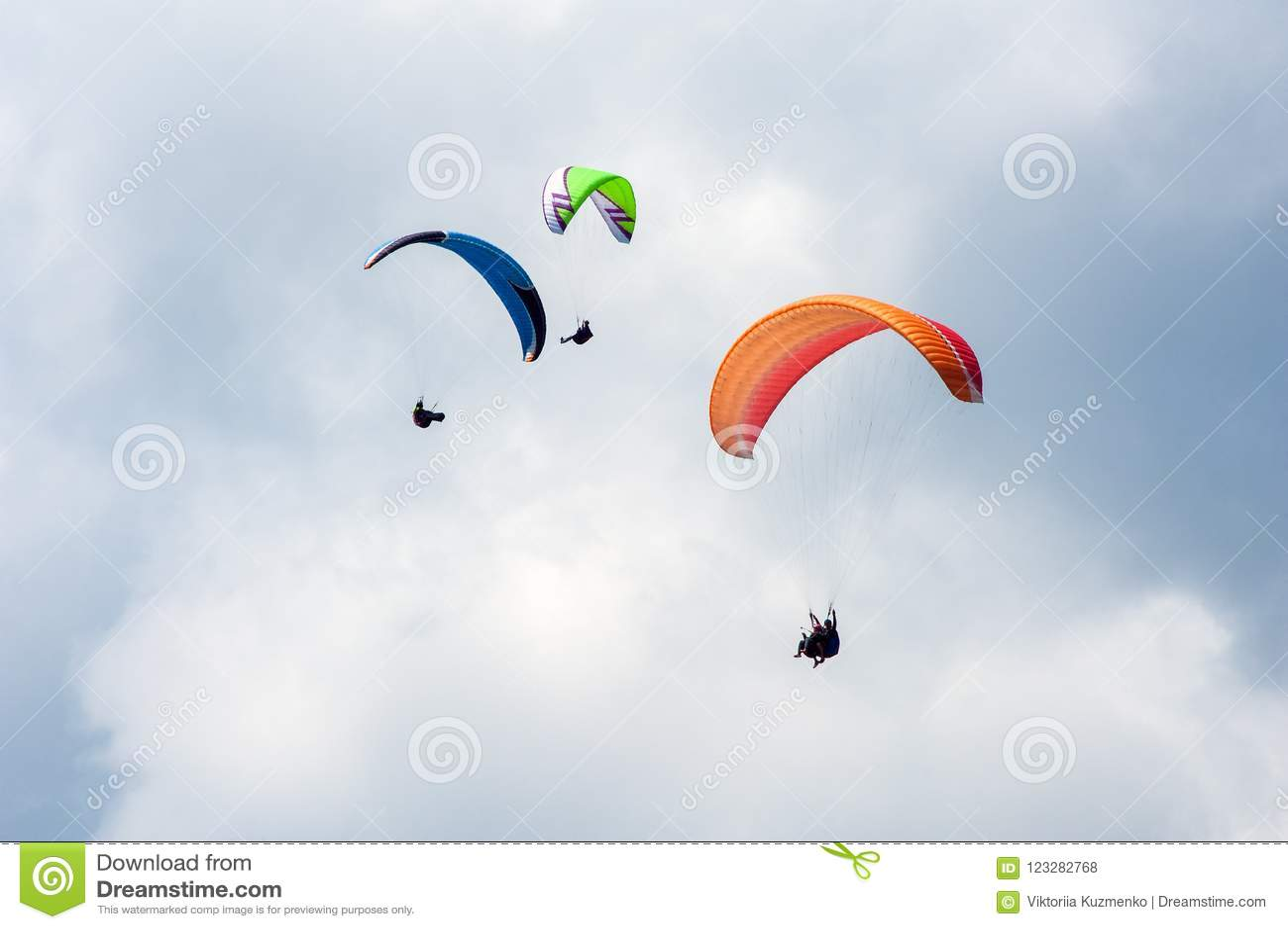 飞行在蓝天的三个滑翔伞以云彩为背景