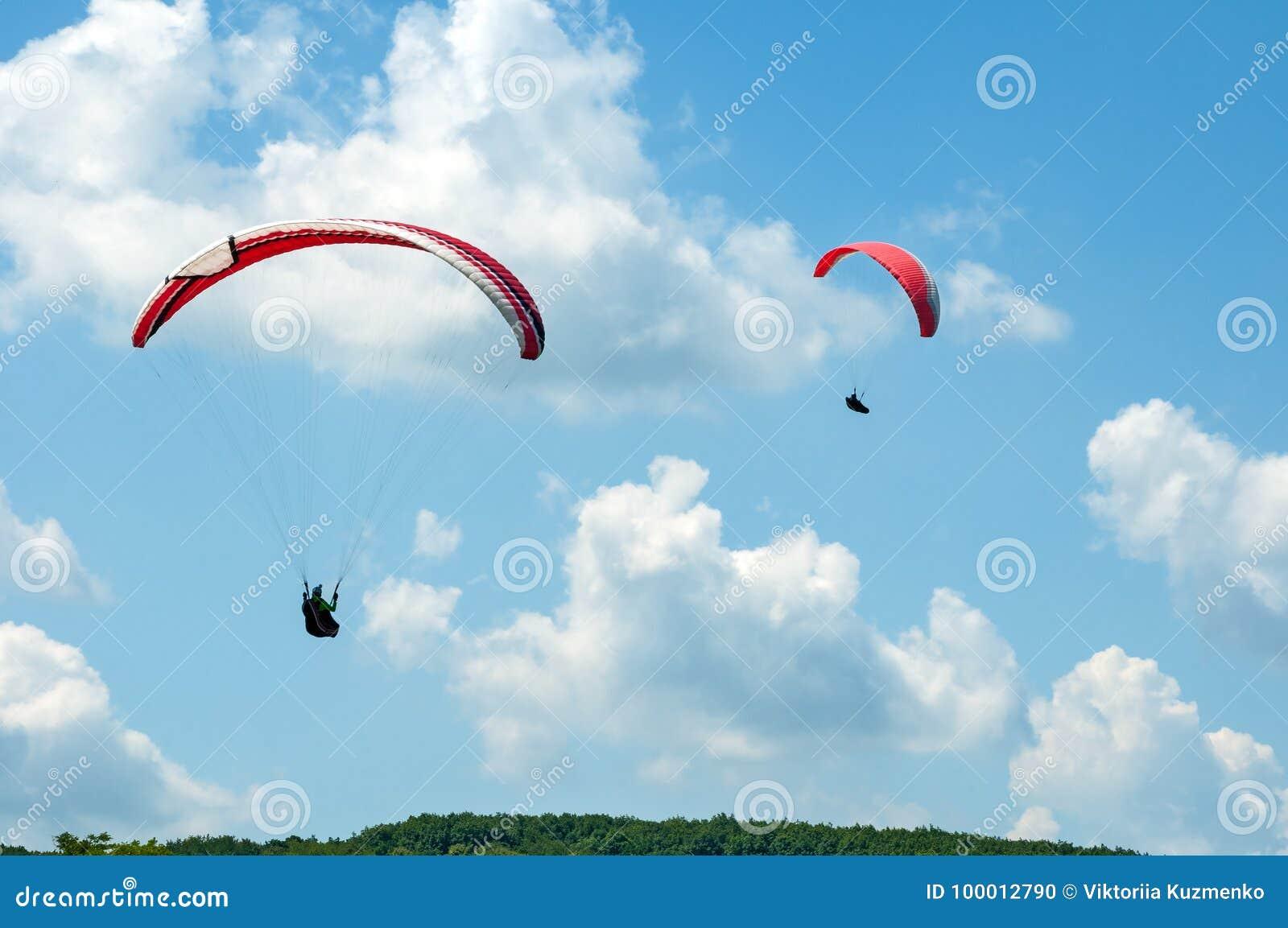 飞行在蓝天的两个滑翔伞以云彩为背景