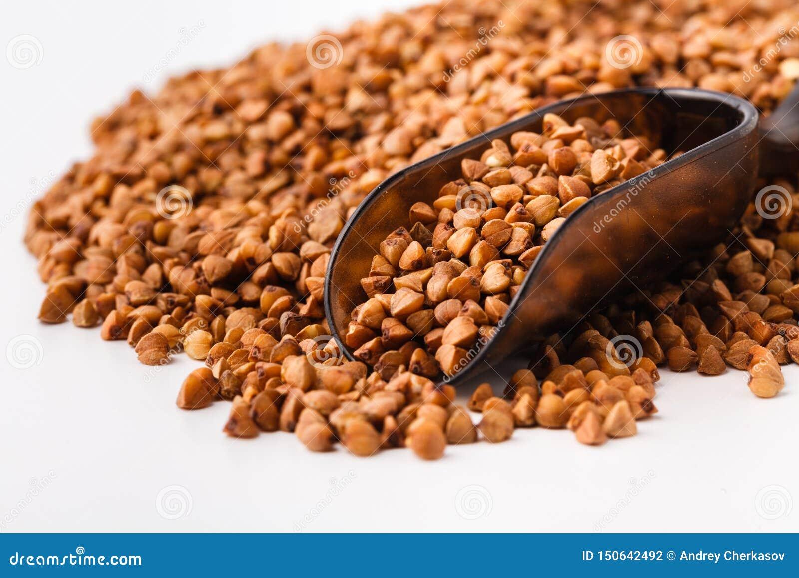 食品成分:荞麦堆在一个木瓢的,在白色背景