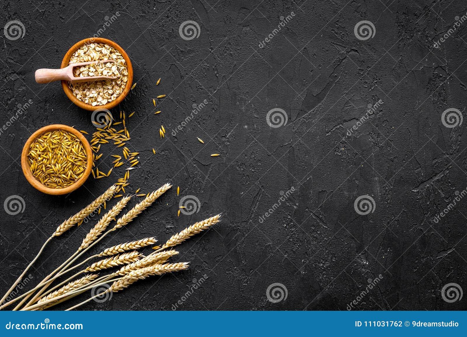 食物有慢碳水化合物的富有 燕麦粥和燕麦在碗在麦子附近小树枝在黑背景顶视图复制