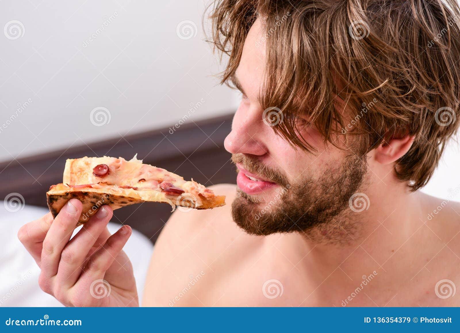 食物送货业务 性感的人吃说谎在床上的比萨 在家休息与裸体和比萨的年轻人 吃薄饼
