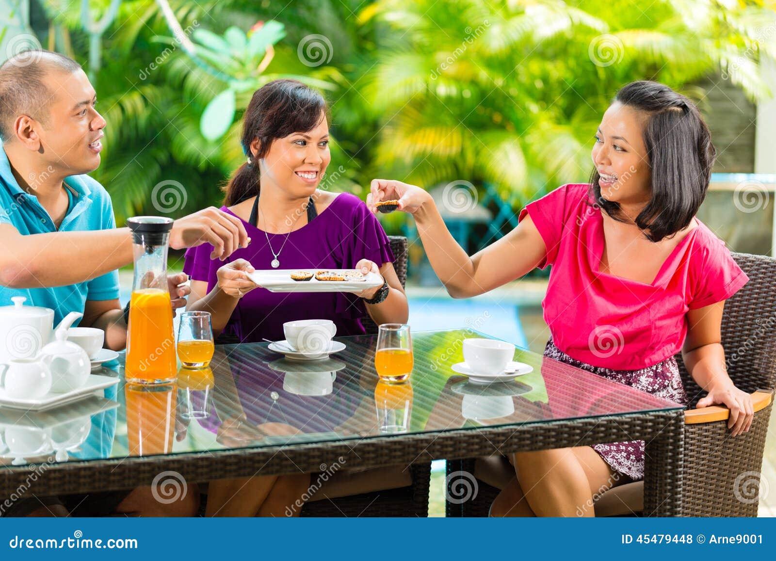 食用亚裔的朋友在家庭门廊的咖啡