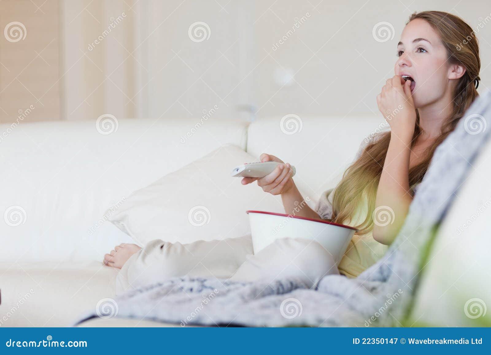 食用的妇女玉米花,当享受电影时