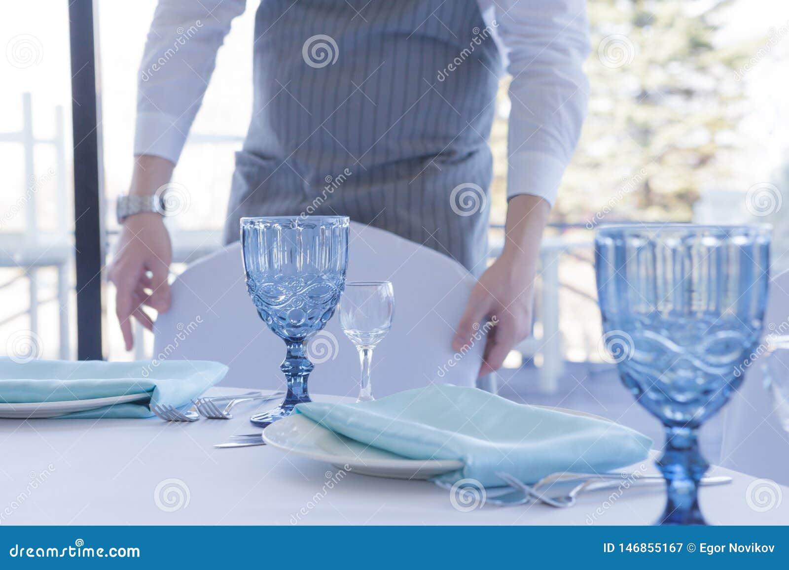 餐馆侍者服务一次婚姻的庆祝的一张桌,移动椅子