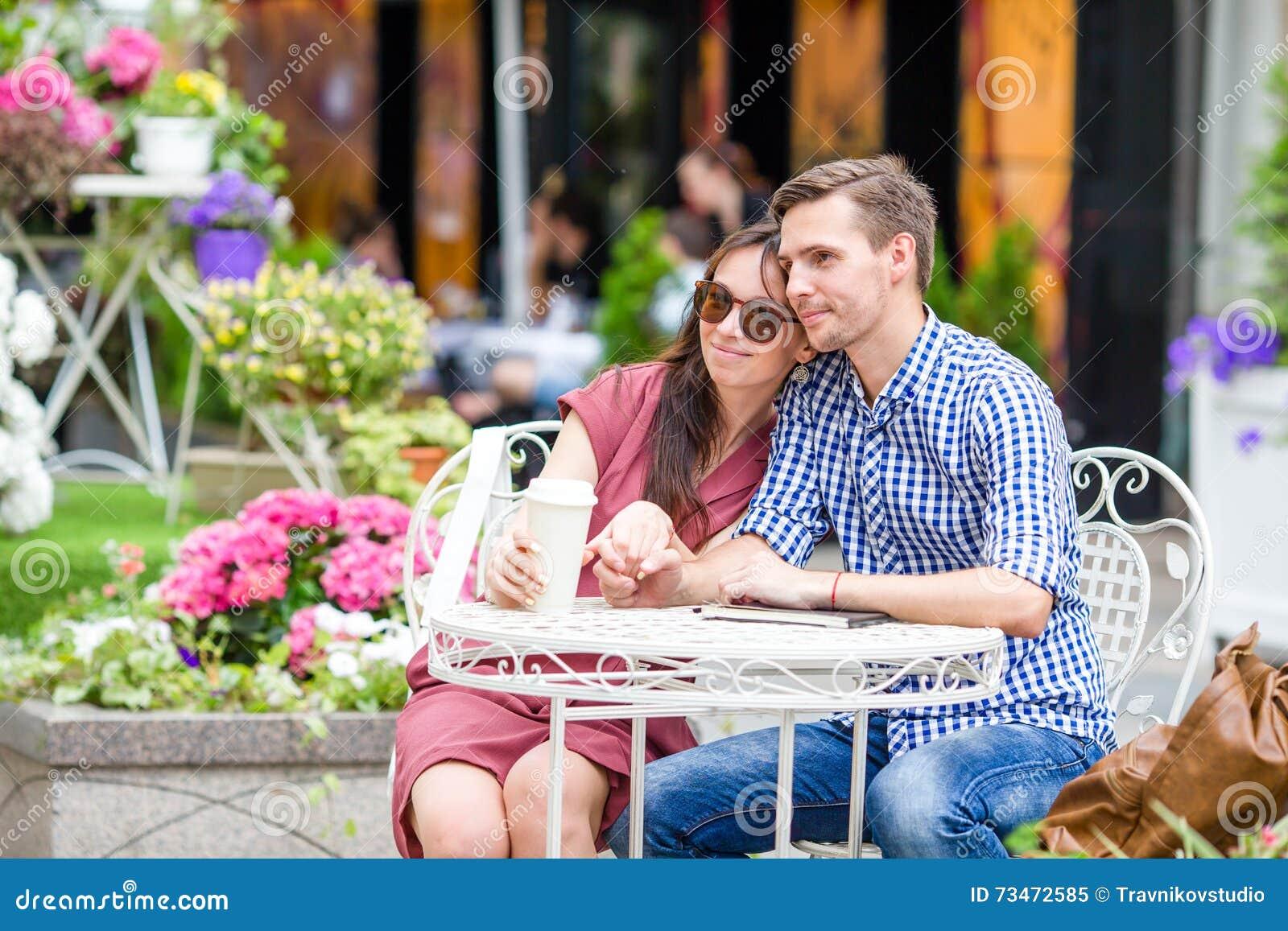 餐馆吃在室外咖啡馆的游人夫妇 少妇享受与她的丈夫的时间,而人读书