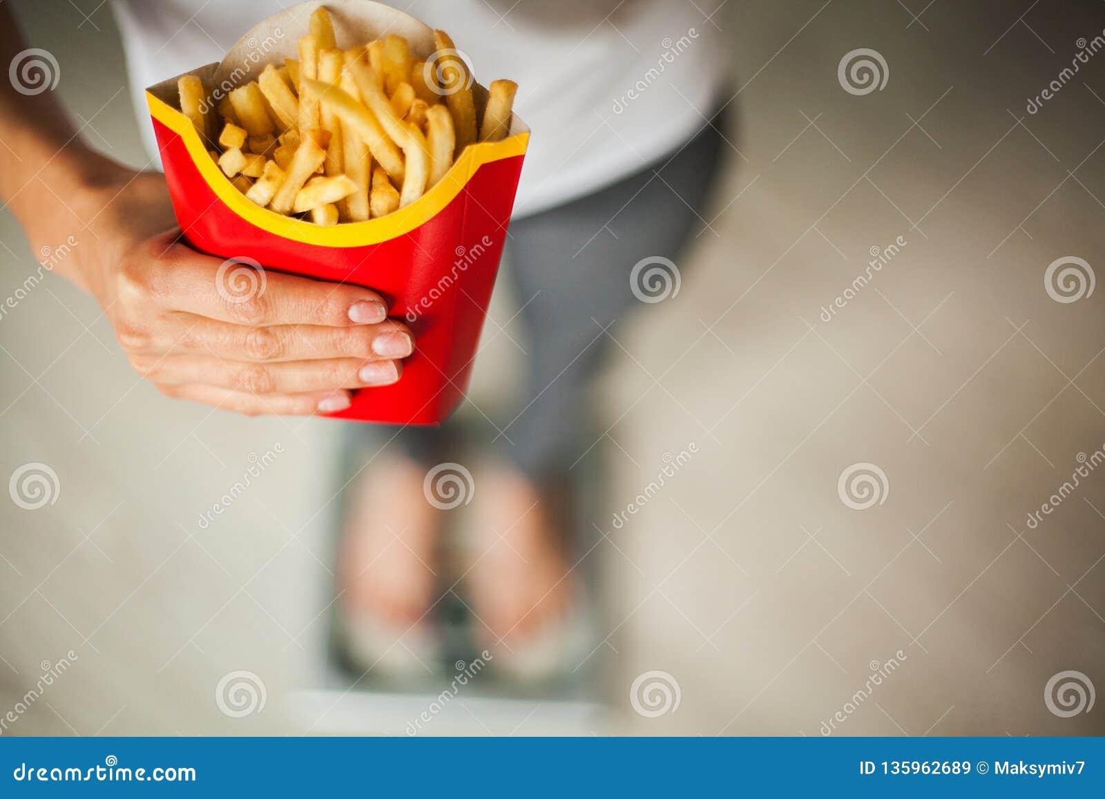 饮食 在拿着不健康的垃圾食品的秤的妇女测量的体重 查出的损失评定躯干重量白人妇女 肥胖病 顶视图