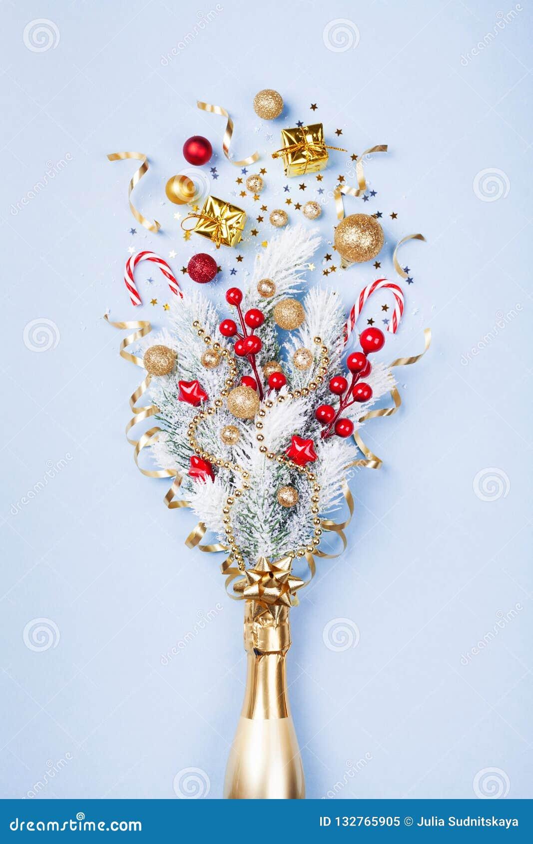 香宾有五彩纸屑、礼物和圣诞装饰的瓶烟花在淡色蓝色背景 平的位置