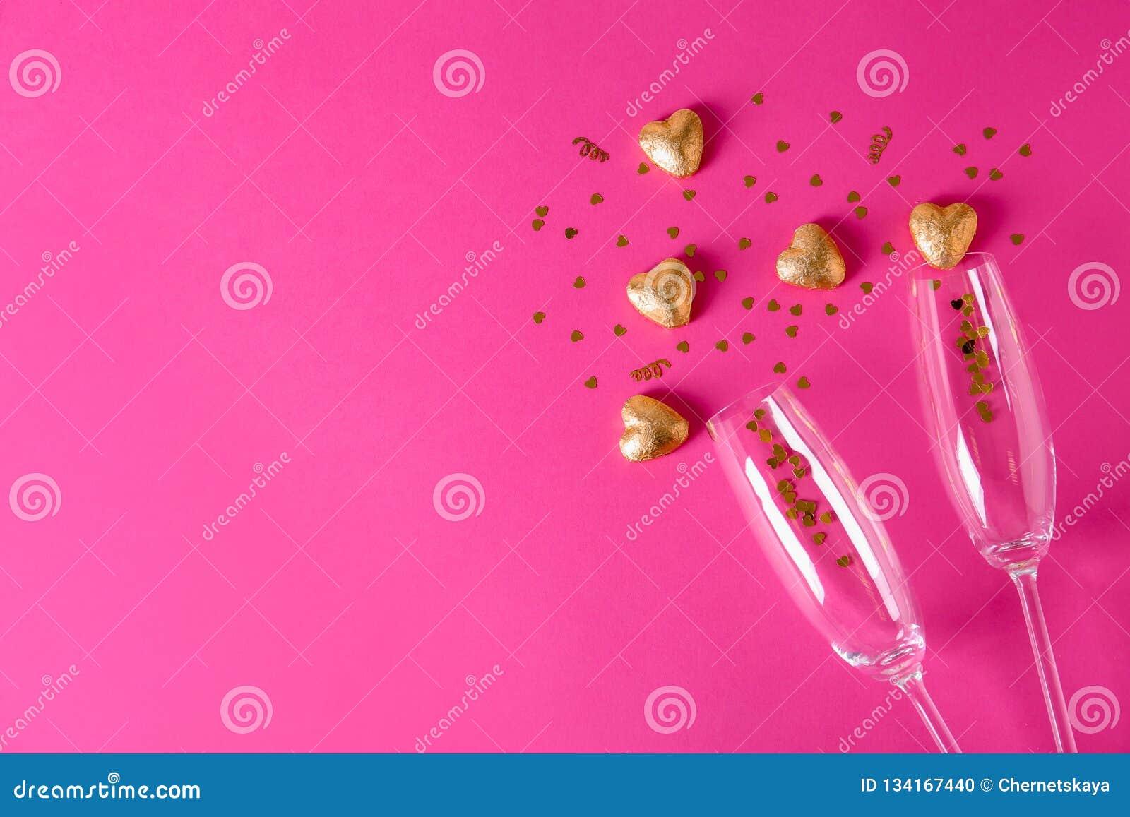 香宾玻璃和心形的糖果在金黄箔在颜色背景