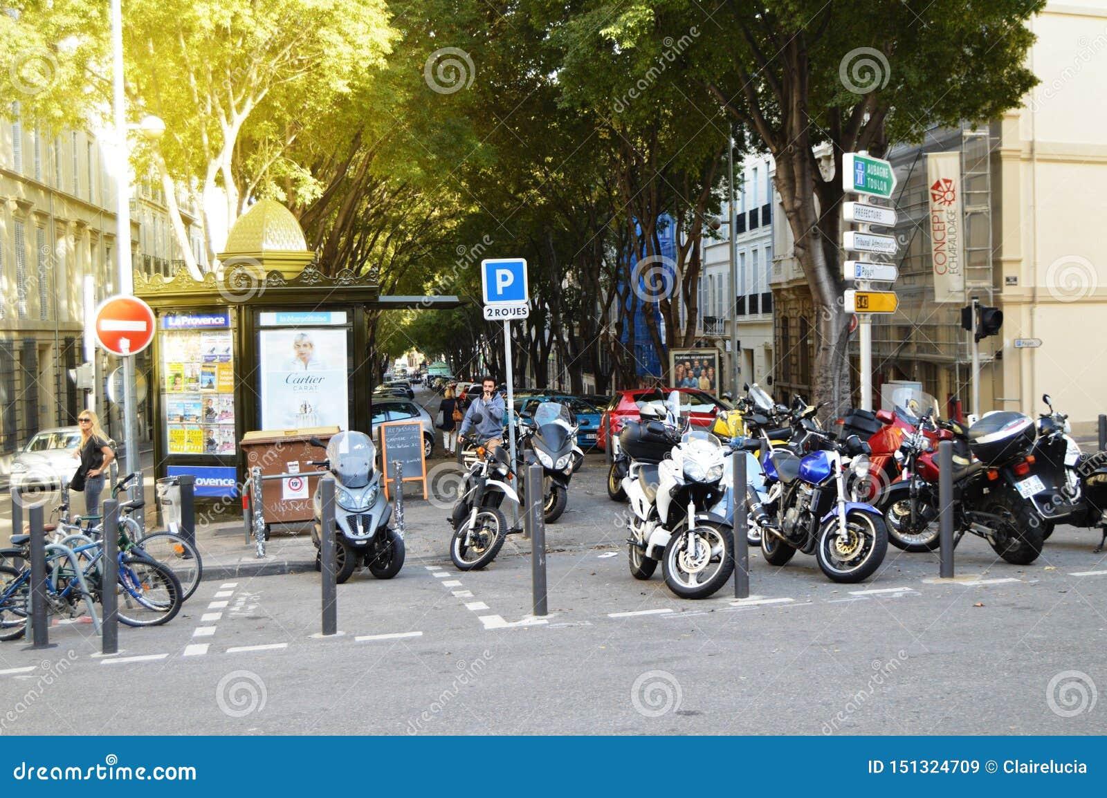 马赛,法国,2018年10月12日 众多的摩托车和滑行车在边路,秋天都市风景旁边停放