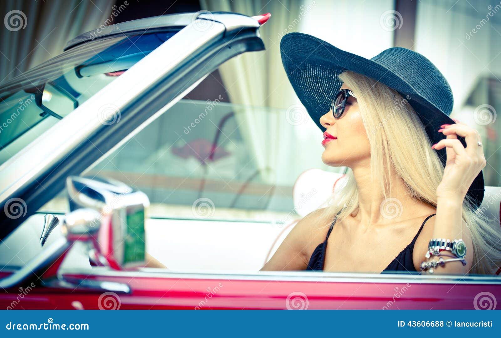 驾驶一辆敞篷车红色减速火箭的汽车的时髦的白肤金发的葡萄酒妇女室外夏天画象  时兴的可爱的公平的头发女孩