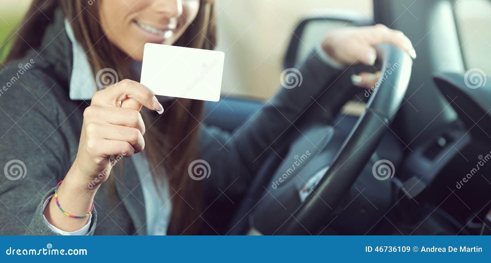 驾驶和拿着名片的少妇