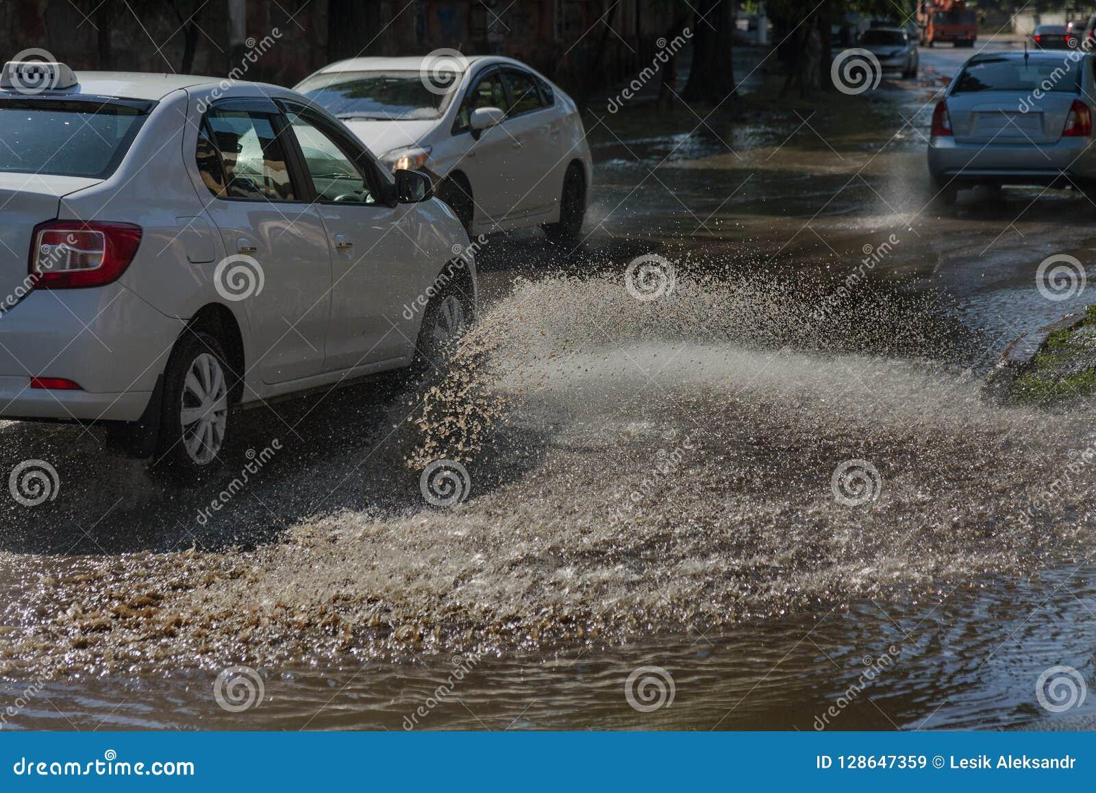 驾驶在一条被充斥的路的汽车在雨造成的洪水期间猛冲 在水的汽车浮游物,充斥街道 在机器的飞溅