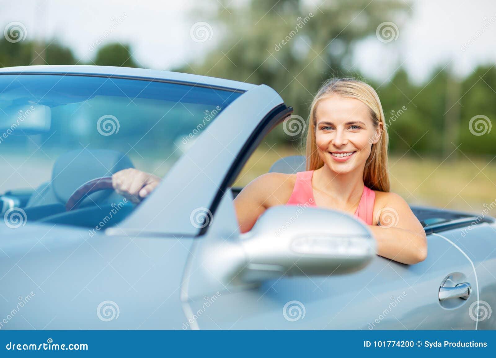 驾驶敞篷车汽车的愉快的少妇