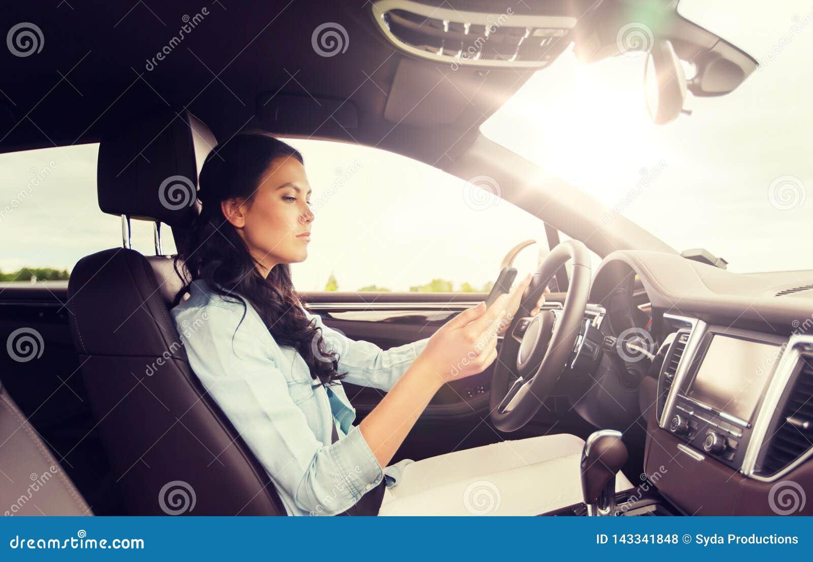 驾驶有smarhphone的妇女汽车
