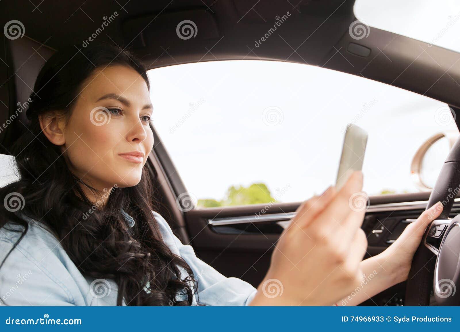 驾驶有smarhphone的愉快的妇女汽车