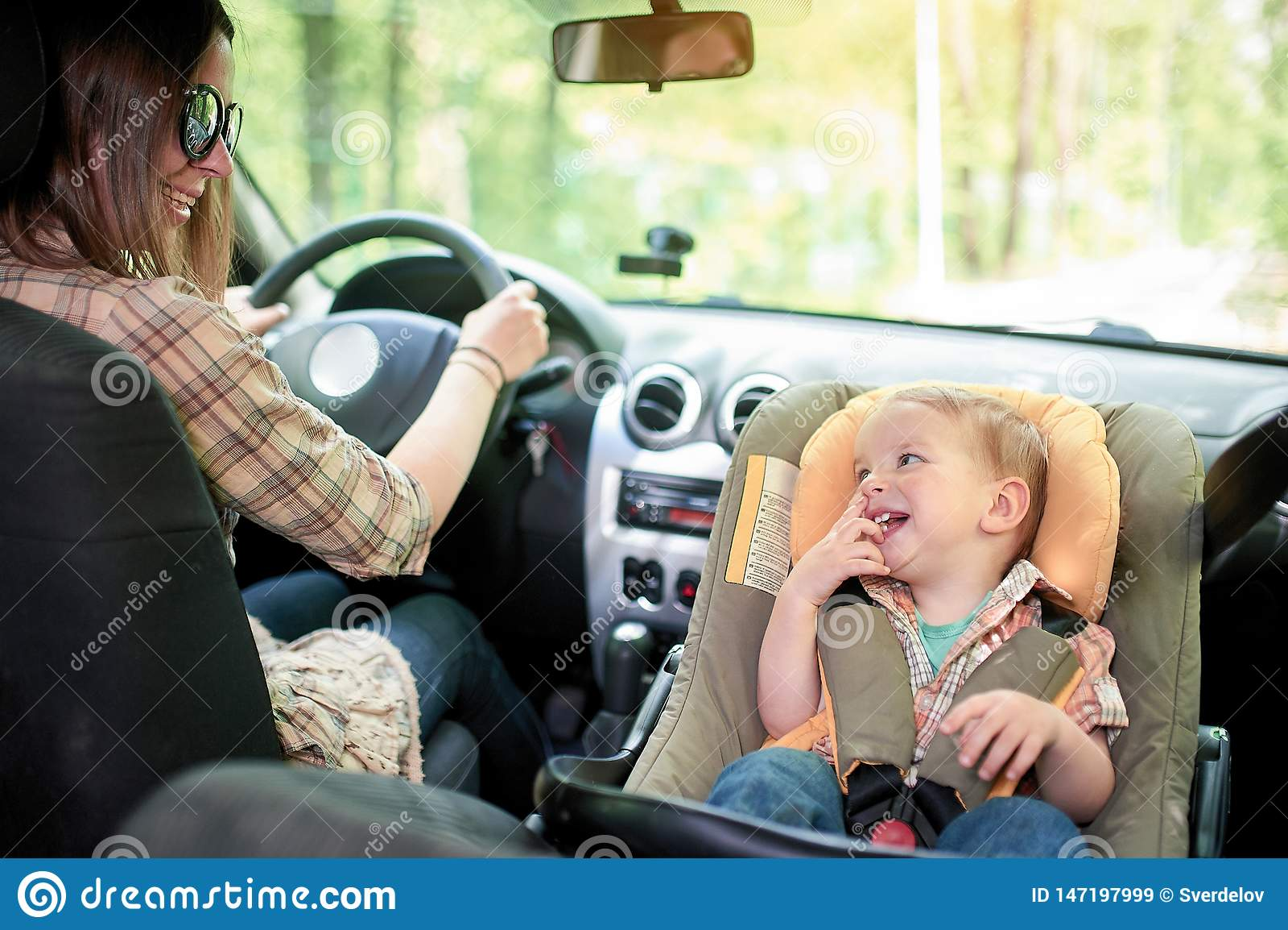 驾驶汽车的年轻美女 在一个前座登上了儿童与一个俏丽的1岁小孩男孩的安全位子