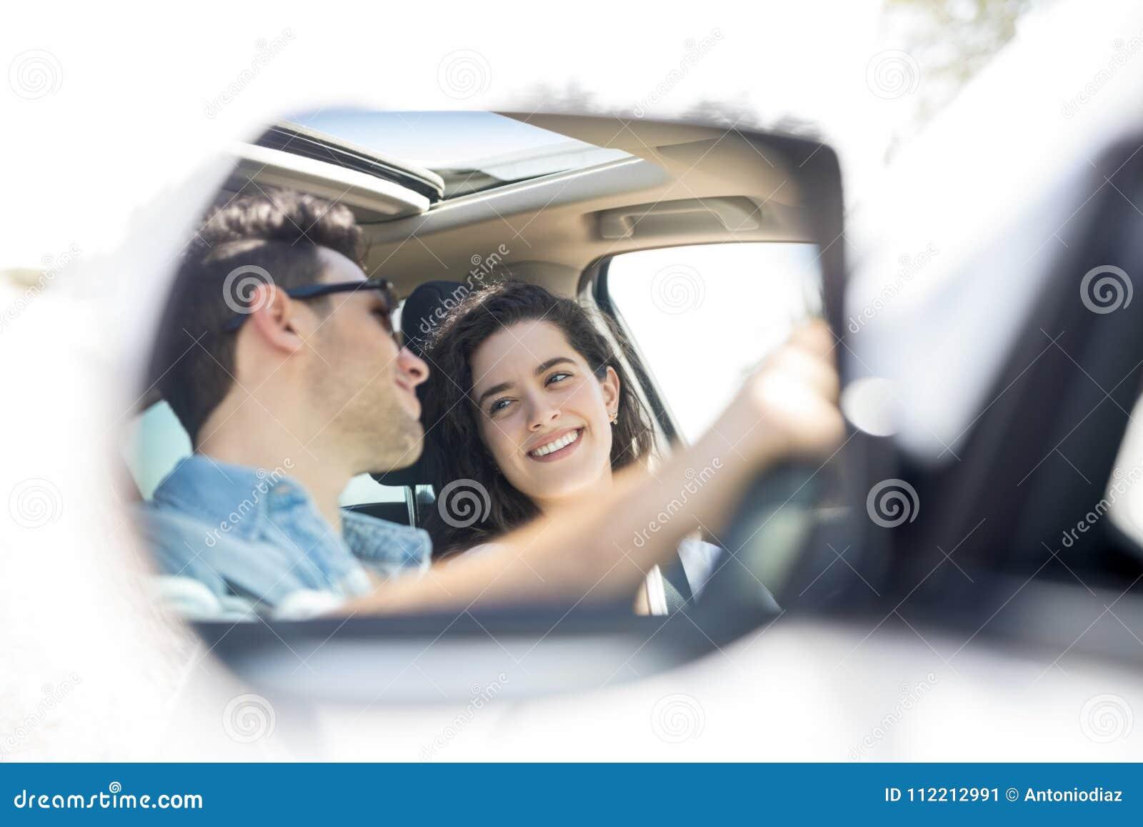 驾驶汽车的愉快的夫妇的后视镜反射