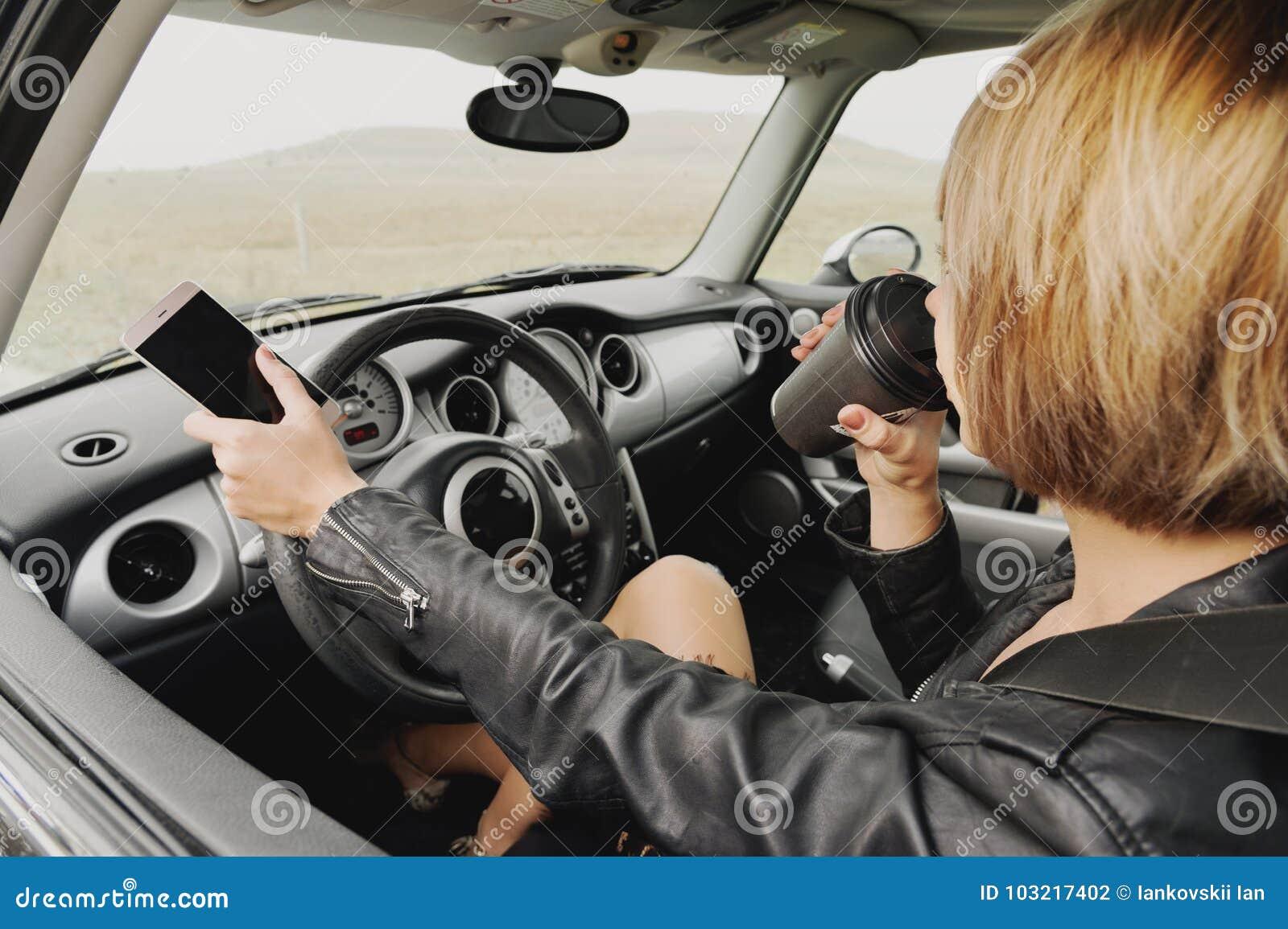 驾驶汽车的皮夹克的企业女孩谈话在电话