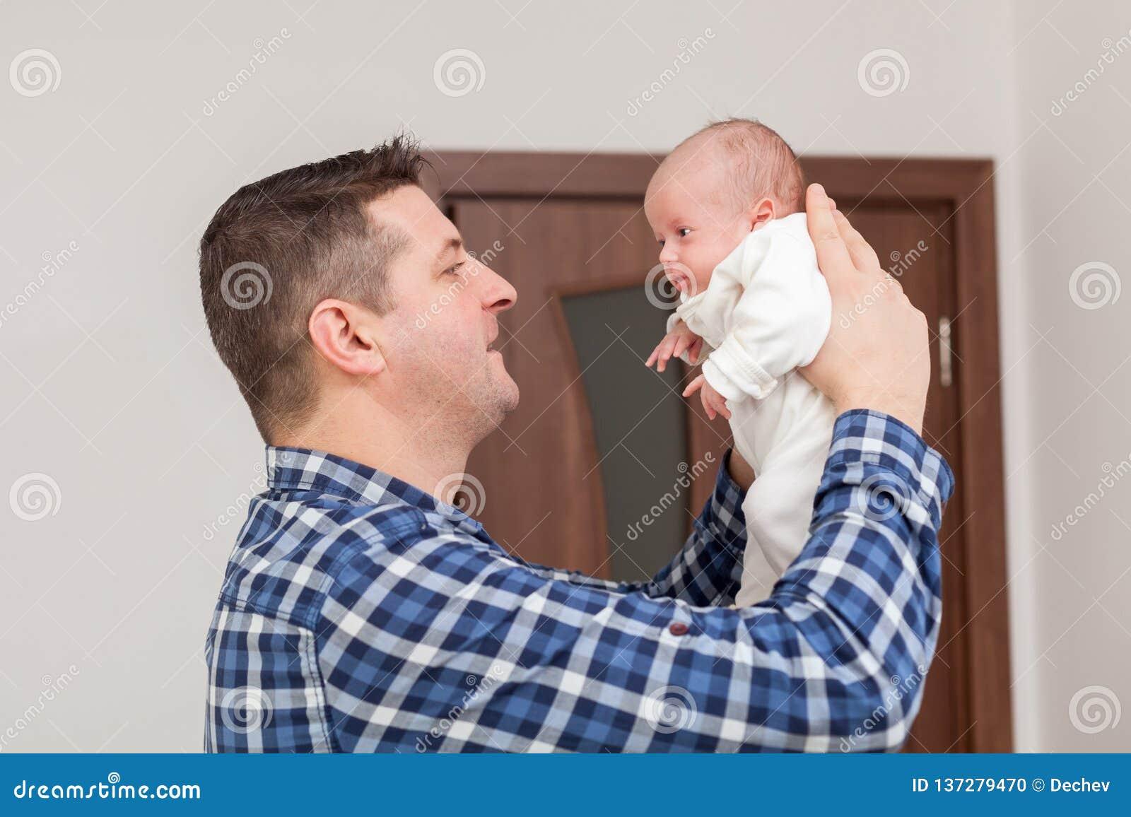 骄傲的父亲在手上的抱着他的新生儿