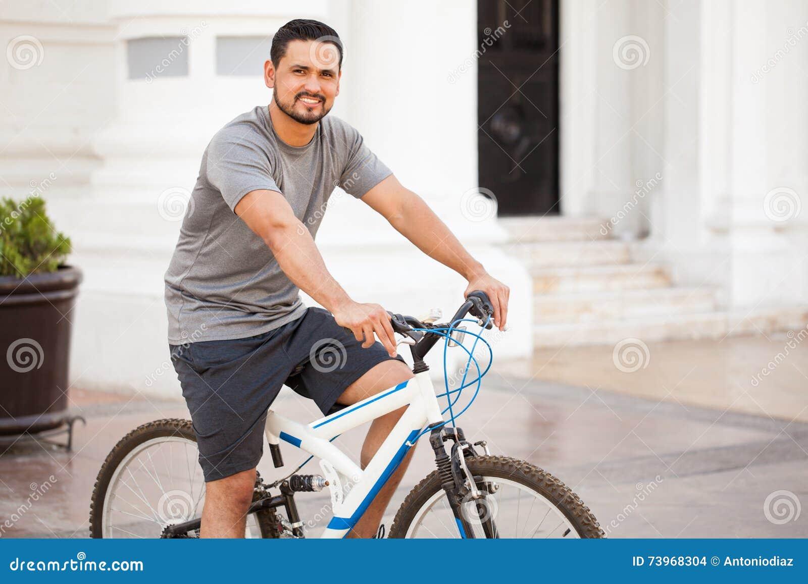 骑一辆自行车的可爱的拉丁人在城市