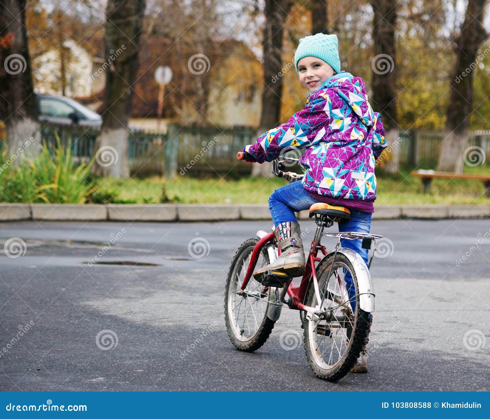 骑一辆自行车的小女孩在秋天公园