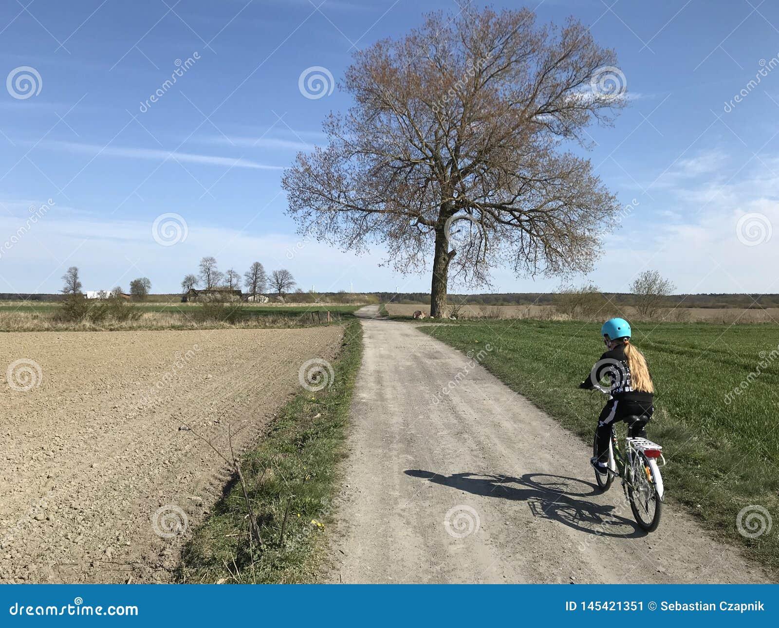 骑一辆自行车的少女在波兰乡下