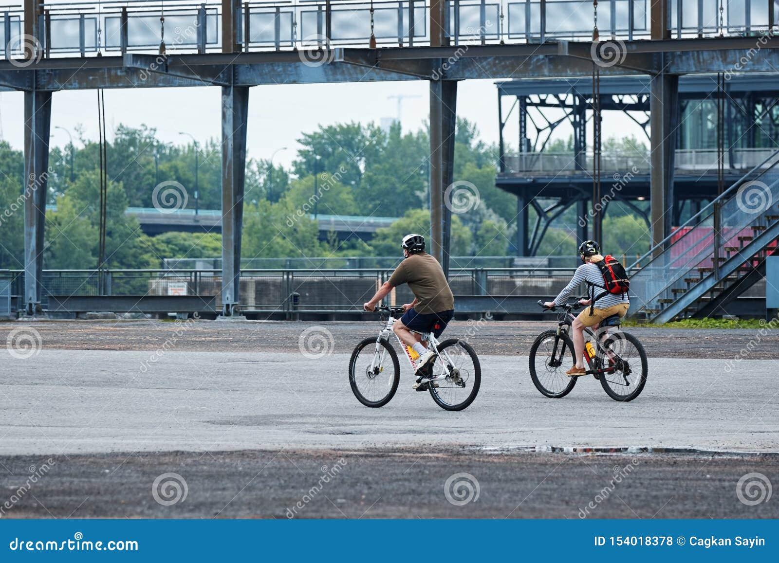骑他们的在旧港口,蒙特利尔,魁北克,加拿大的加拿大夫妇自行车