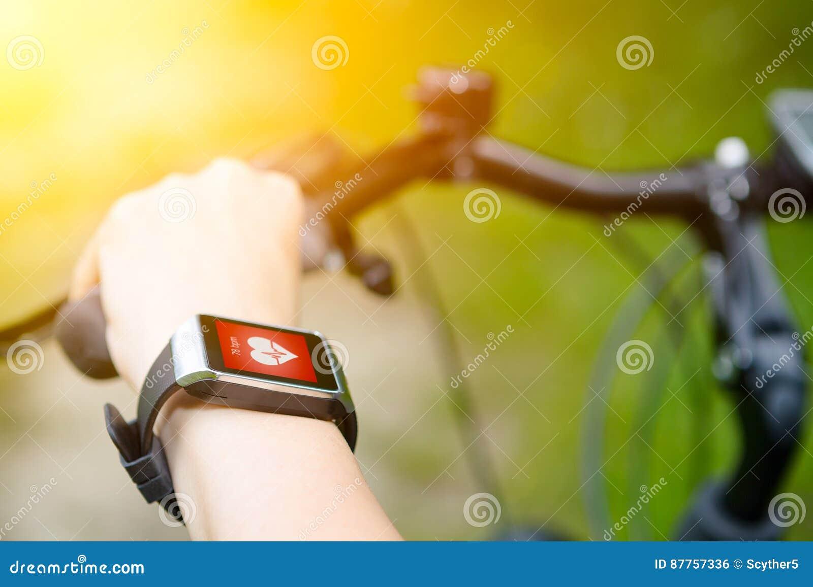骑有smartwatch心率显示器的妇女一辆自行车