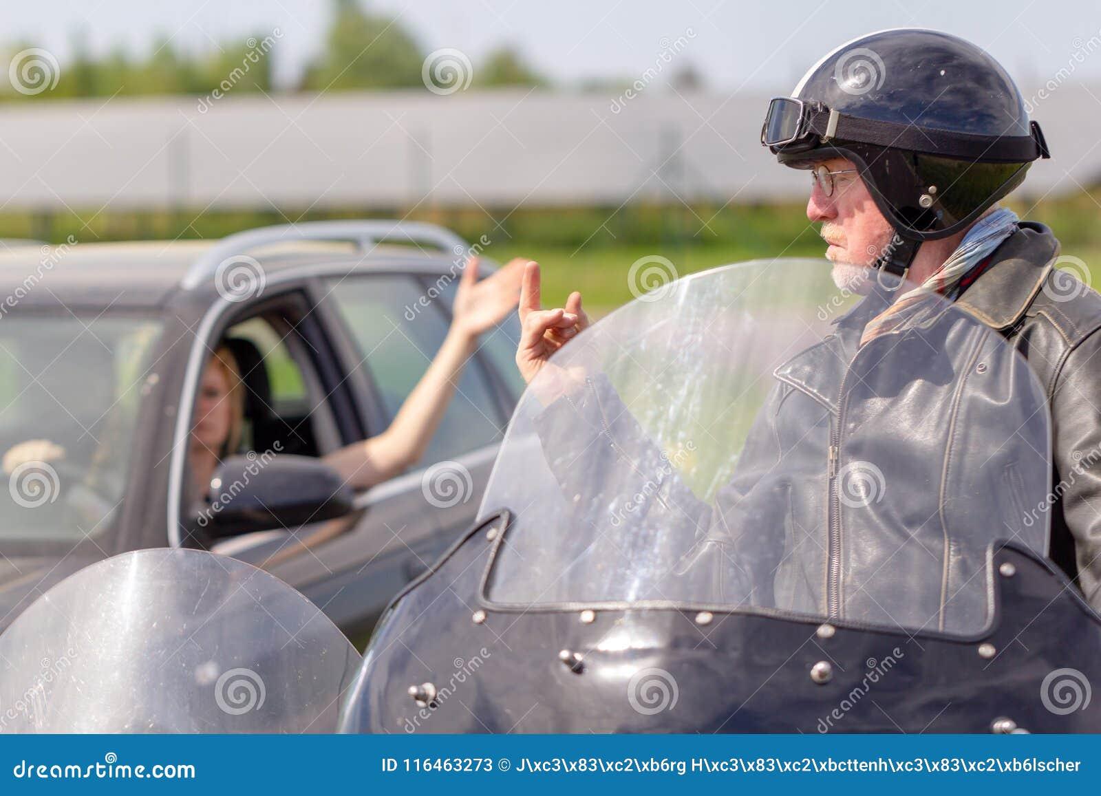 骑自行车的人显示他的中指对汽车司机