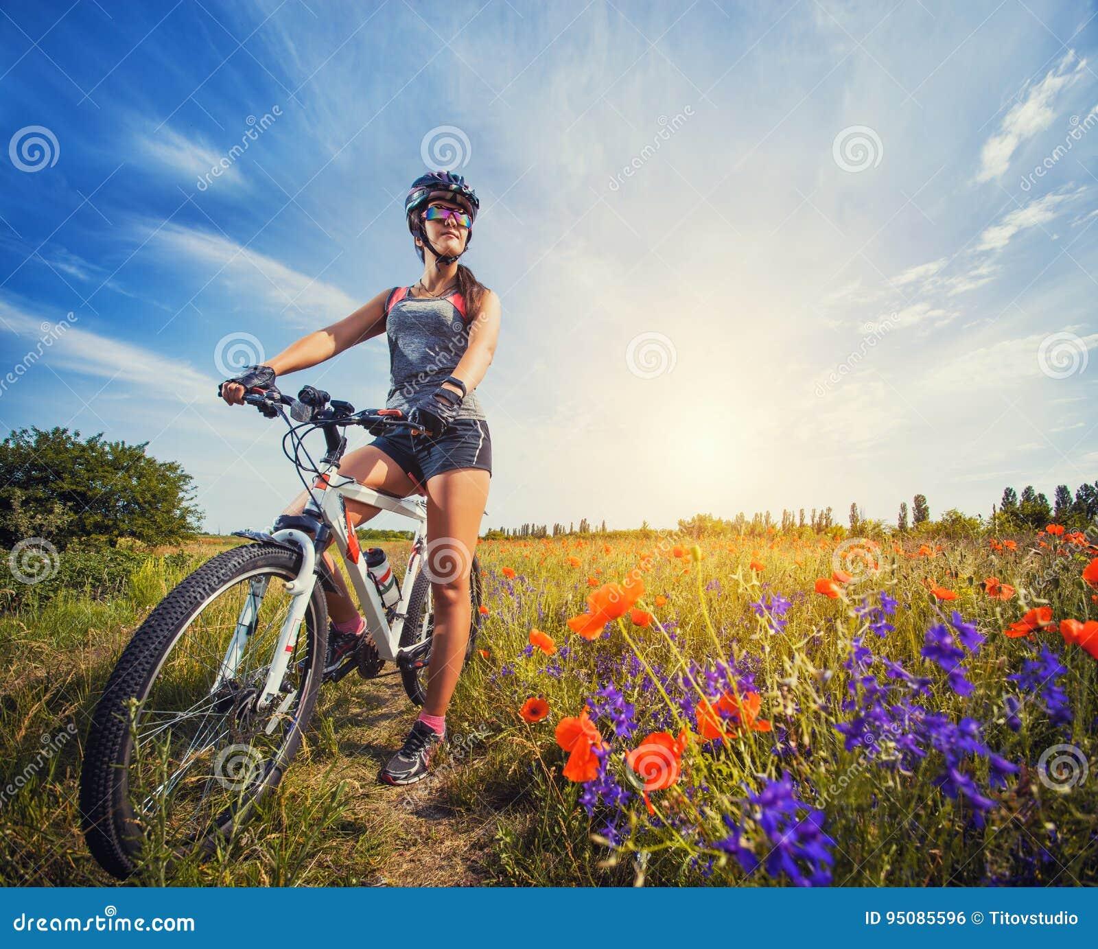 骑自行车的少妇在一个开花的鸦片草甸