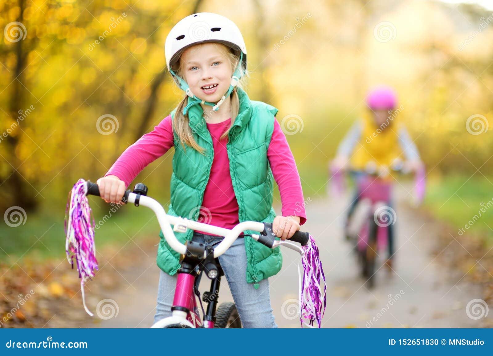 骑自行车的逗人喜爱的妹在城市公园在晴朗的秋天天 r