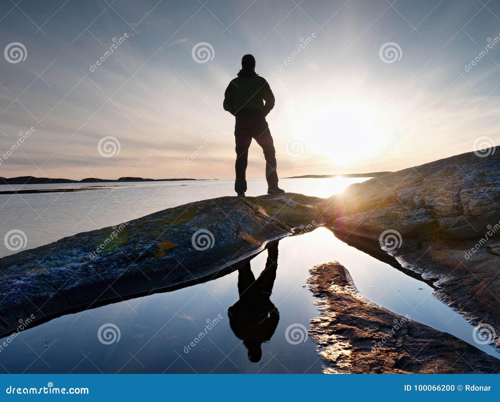 高在海的背包徒步旅行者手表明白晴朗的破晓 远足者远足者享受惊人的日出