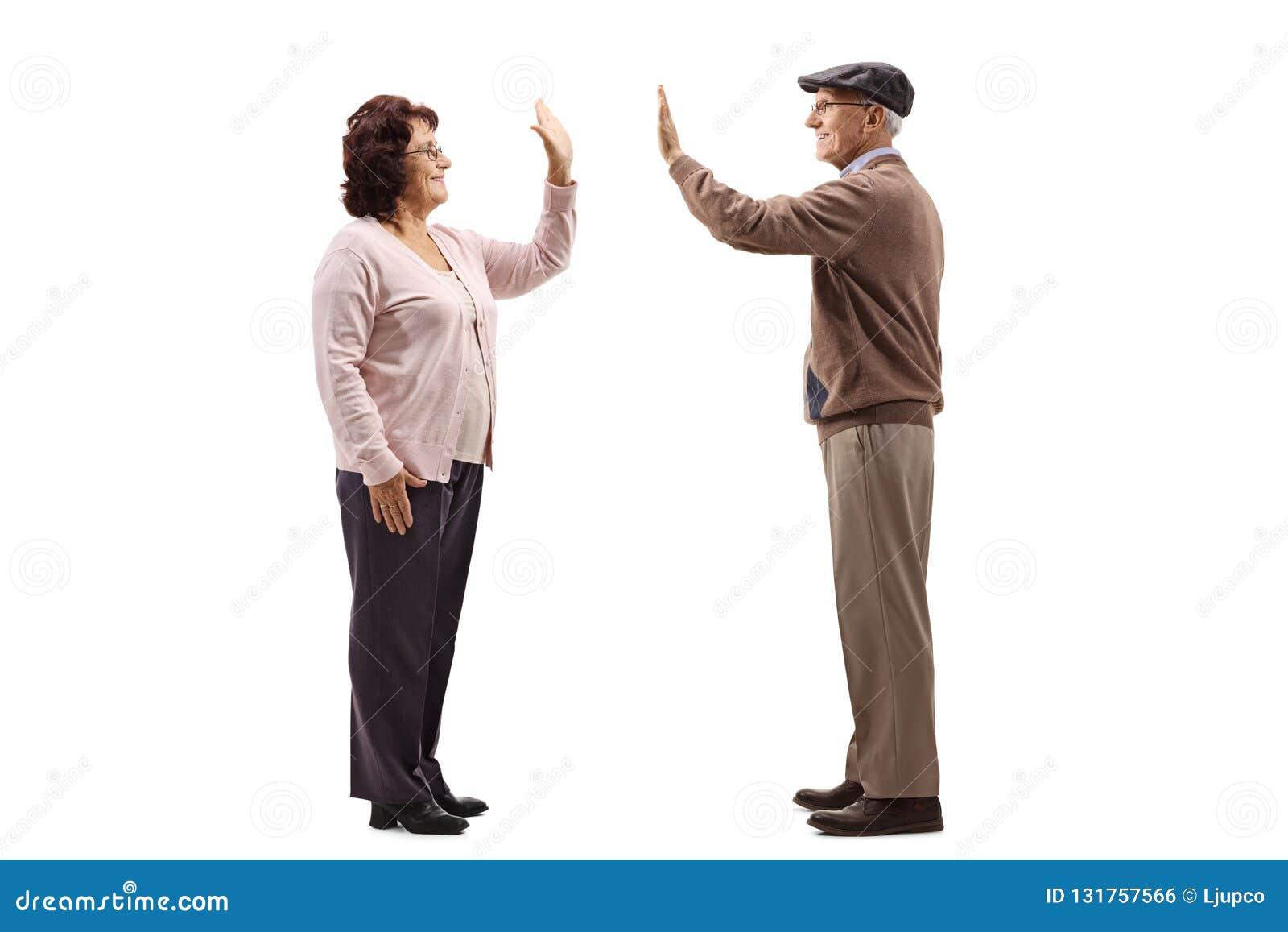 高fiving一名资深的妇女的全长外形射击在白色背景隔绝的一名老人