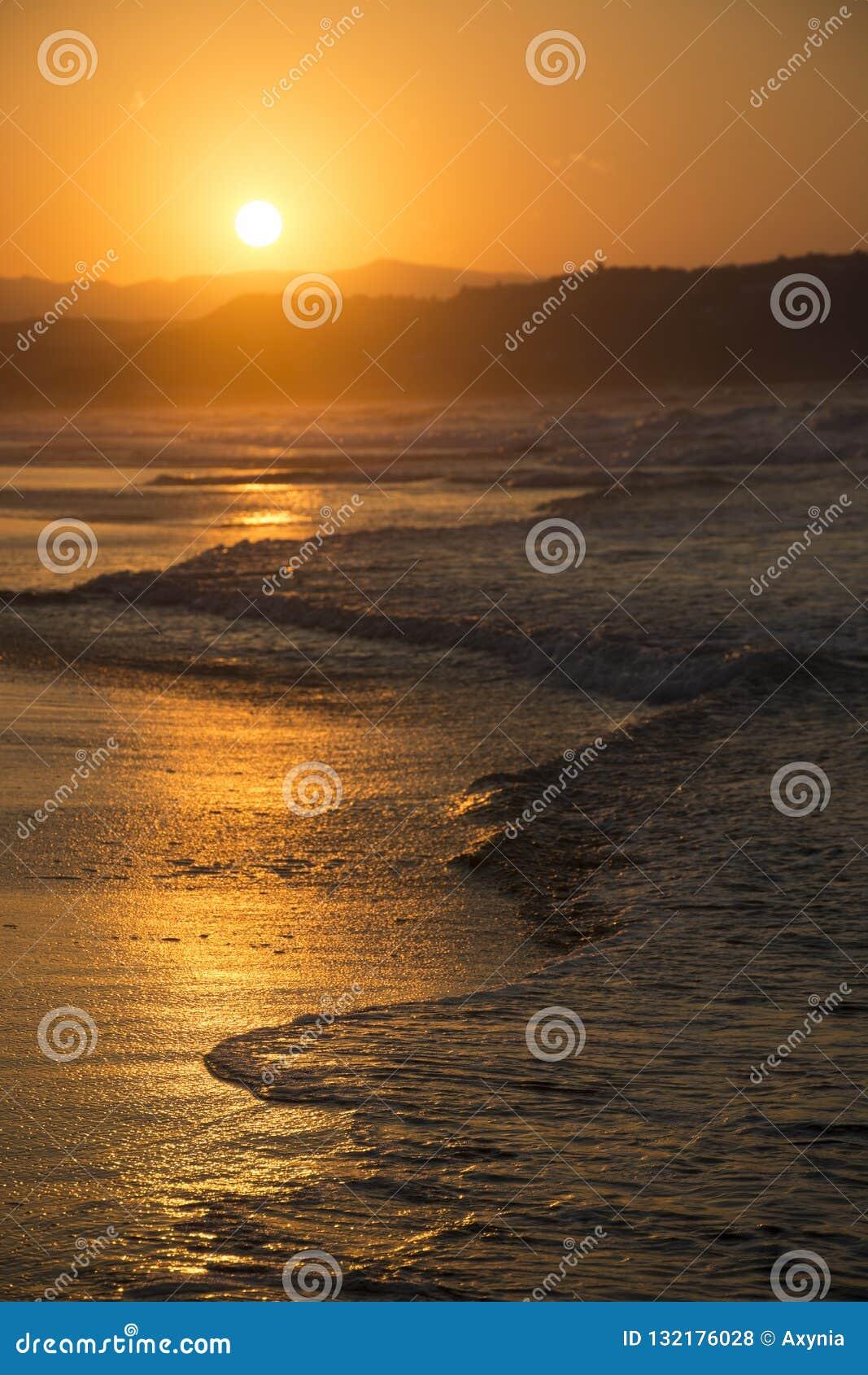 高JPG解决方法海运日落 在黄昏的晴朗的在背景的道路和小山 Georgioupolis海滩,克利特希腊