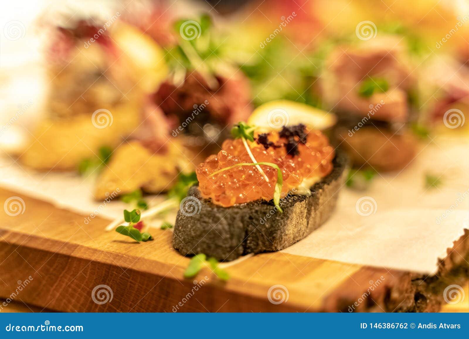 鱼子酱开胃小菜喝酒快餐设置与浅景深在黑暗的难看的东西背景的
