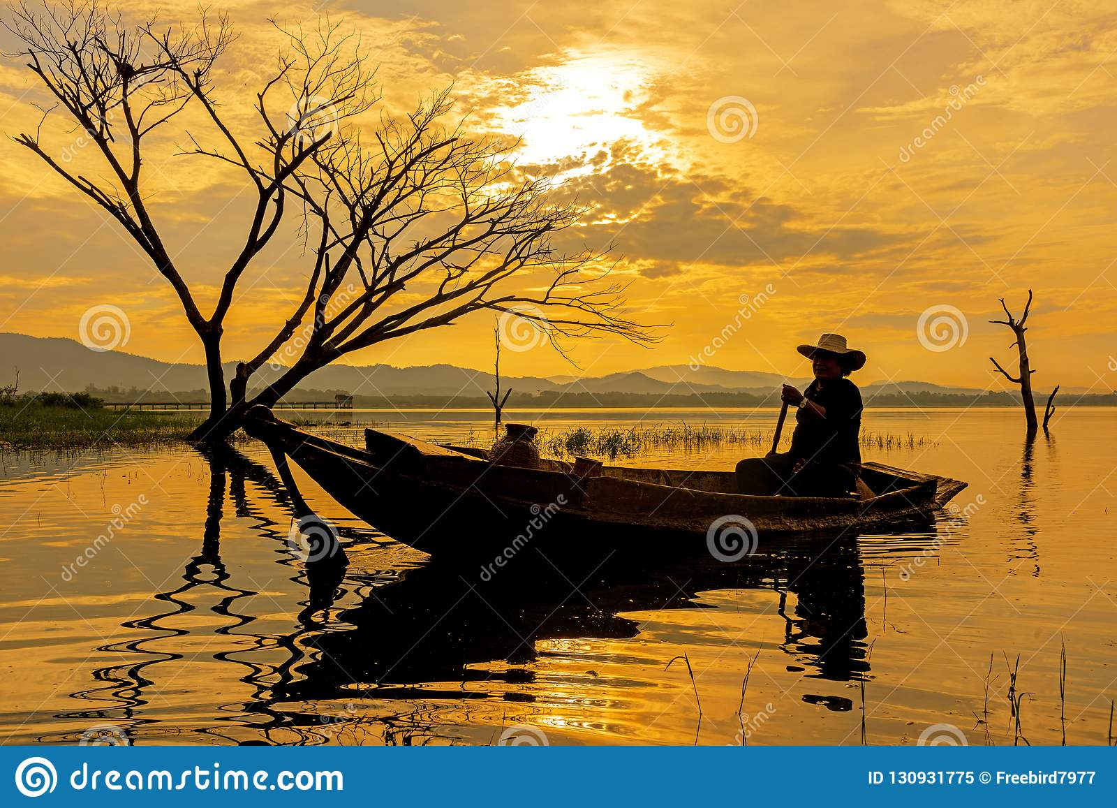 鱼小船的剪影渔夫在湖阳光早晨