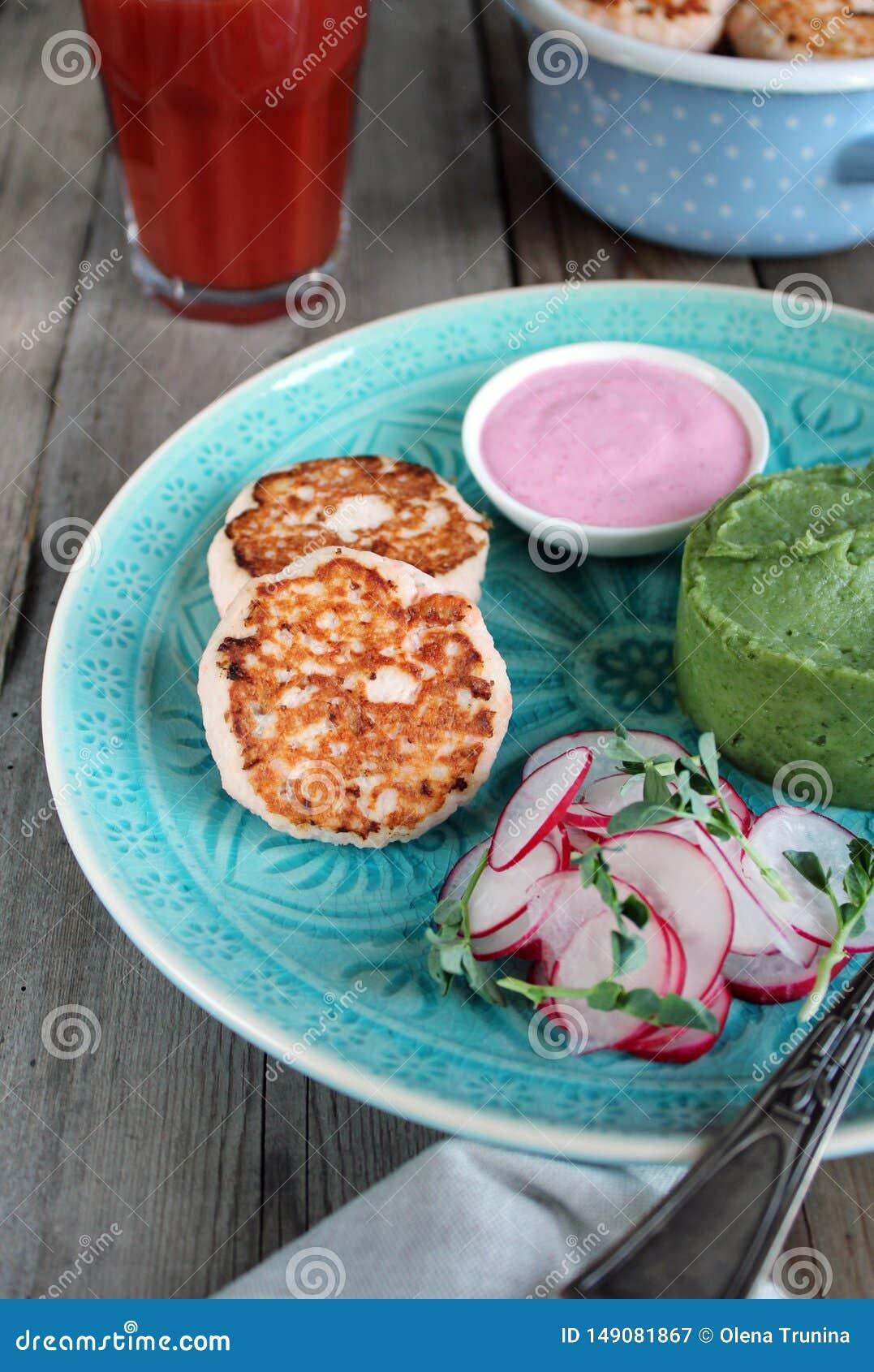 鱼炸肉排用绿色土豆泥 桃红色调味汁和萝卜和microgreens沙拉 西红柿汁