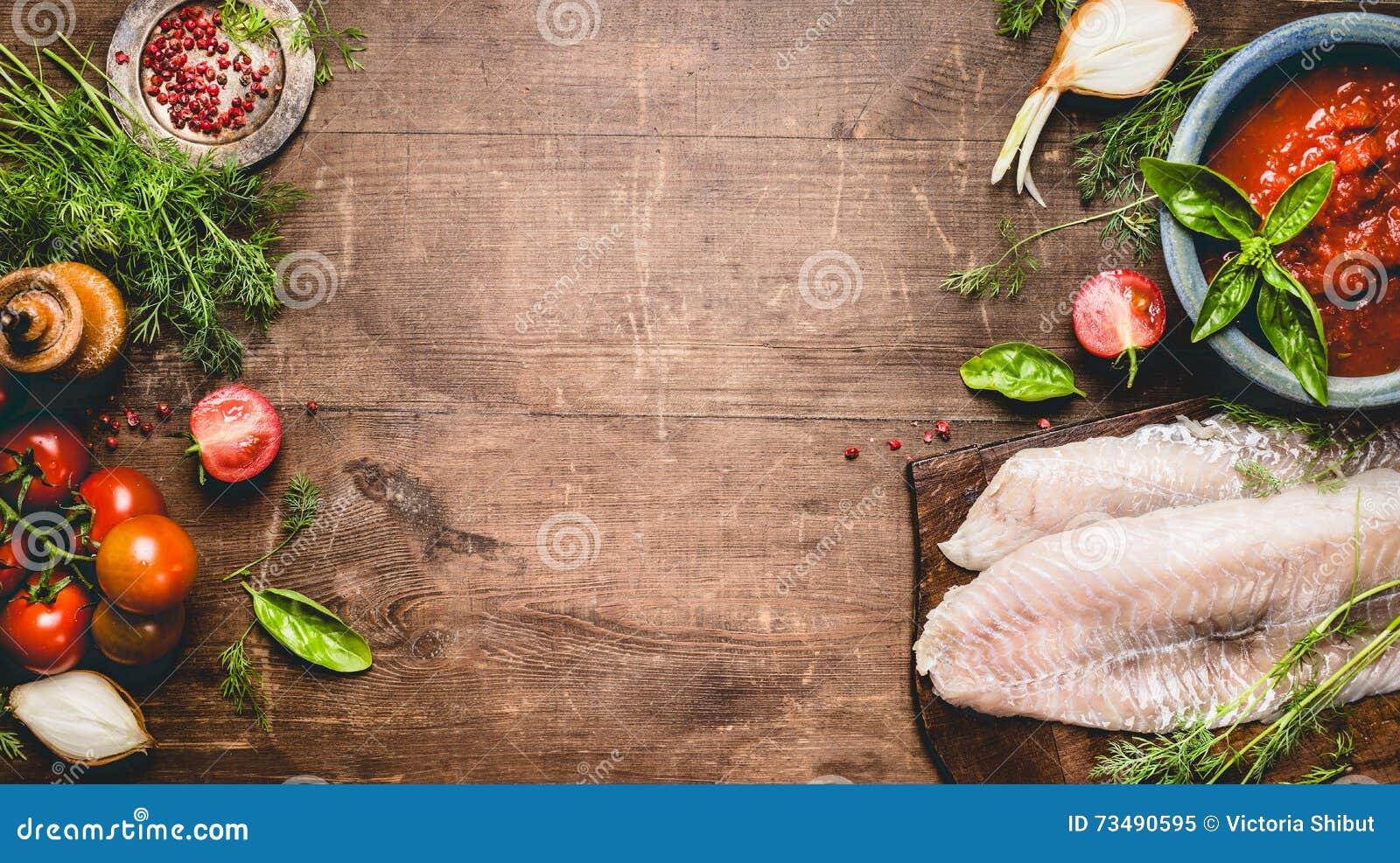 鱼宴烹调 新鲜的生鱼内圆角用蕃茄、调味汁和成份在土气木背景,顶视图,横幅