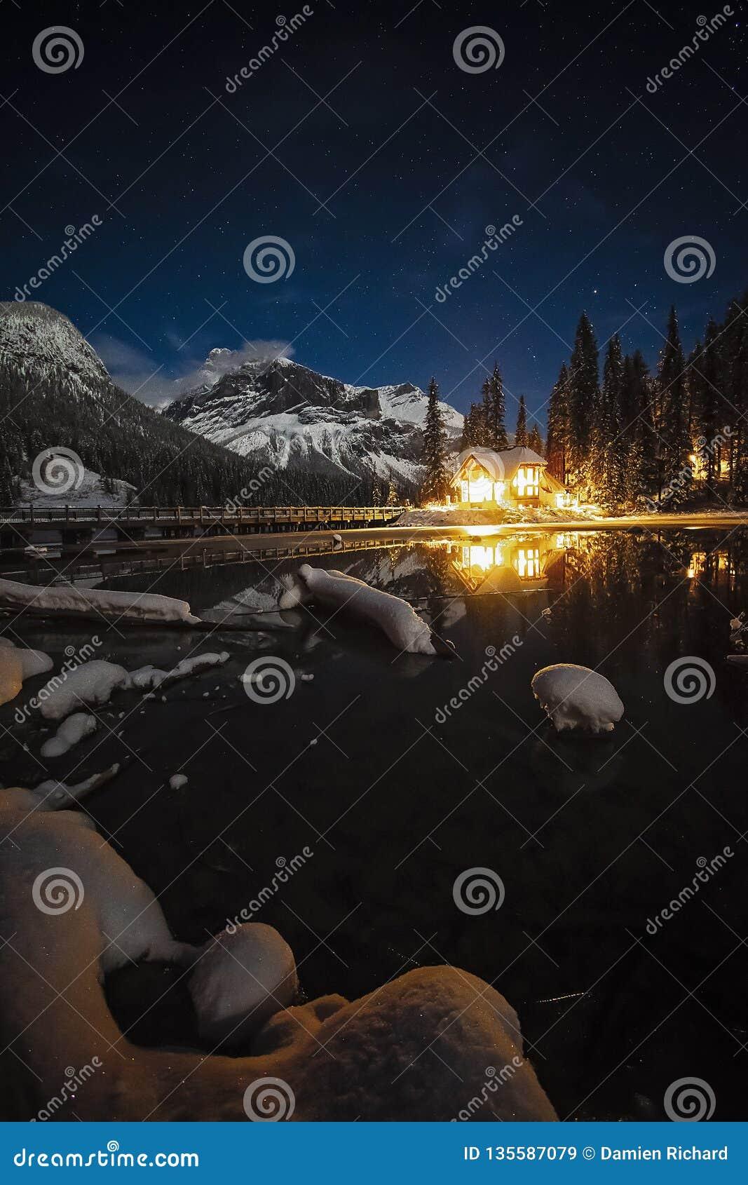 鲜绿色湖小屋在晚上