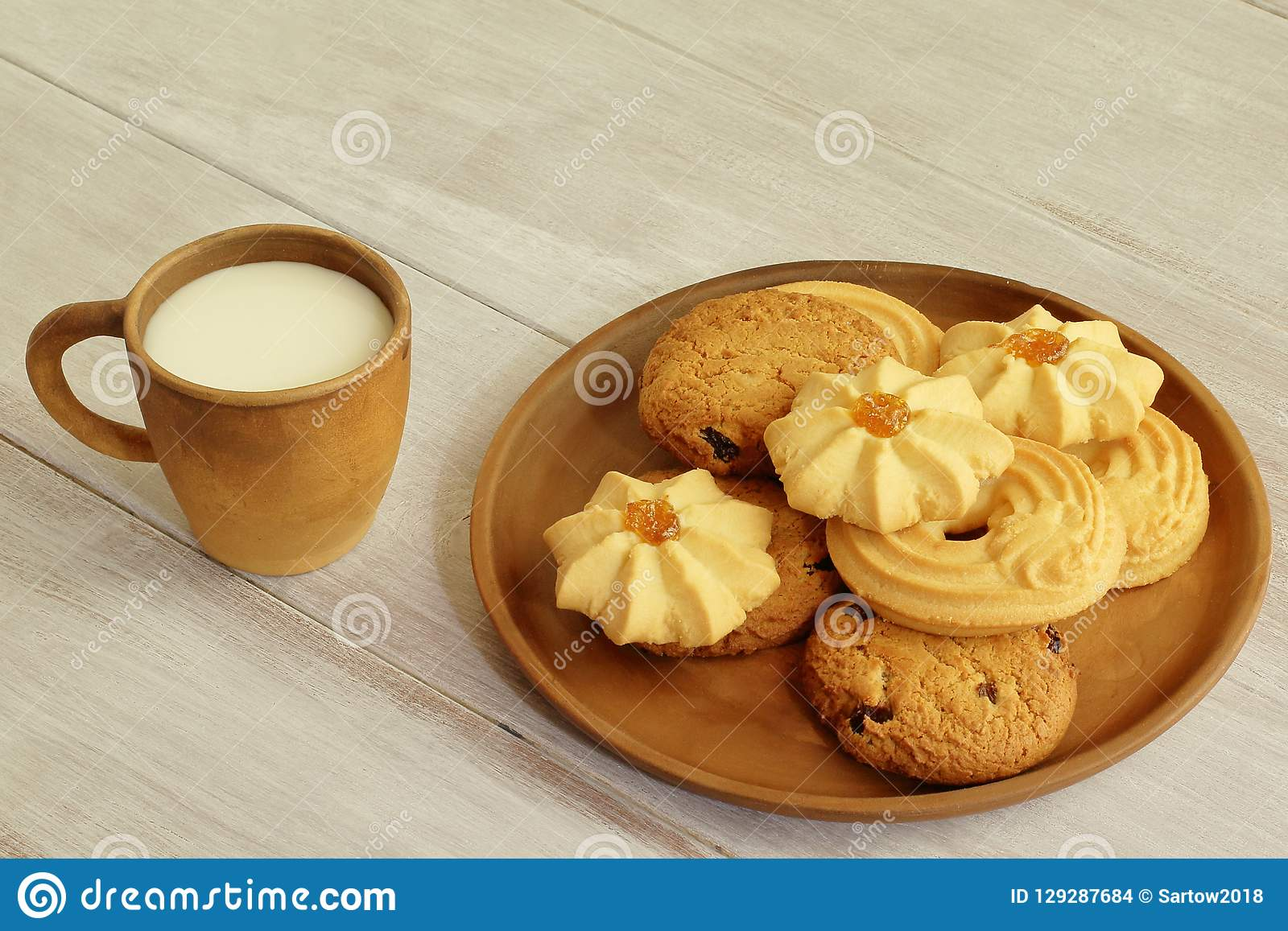 鲜美在黏土杯子和芬芳脆曲奇饼的早餐热的牛奶与葡萄干坚果和果酱在陶瓷板材在浅褐色的woode