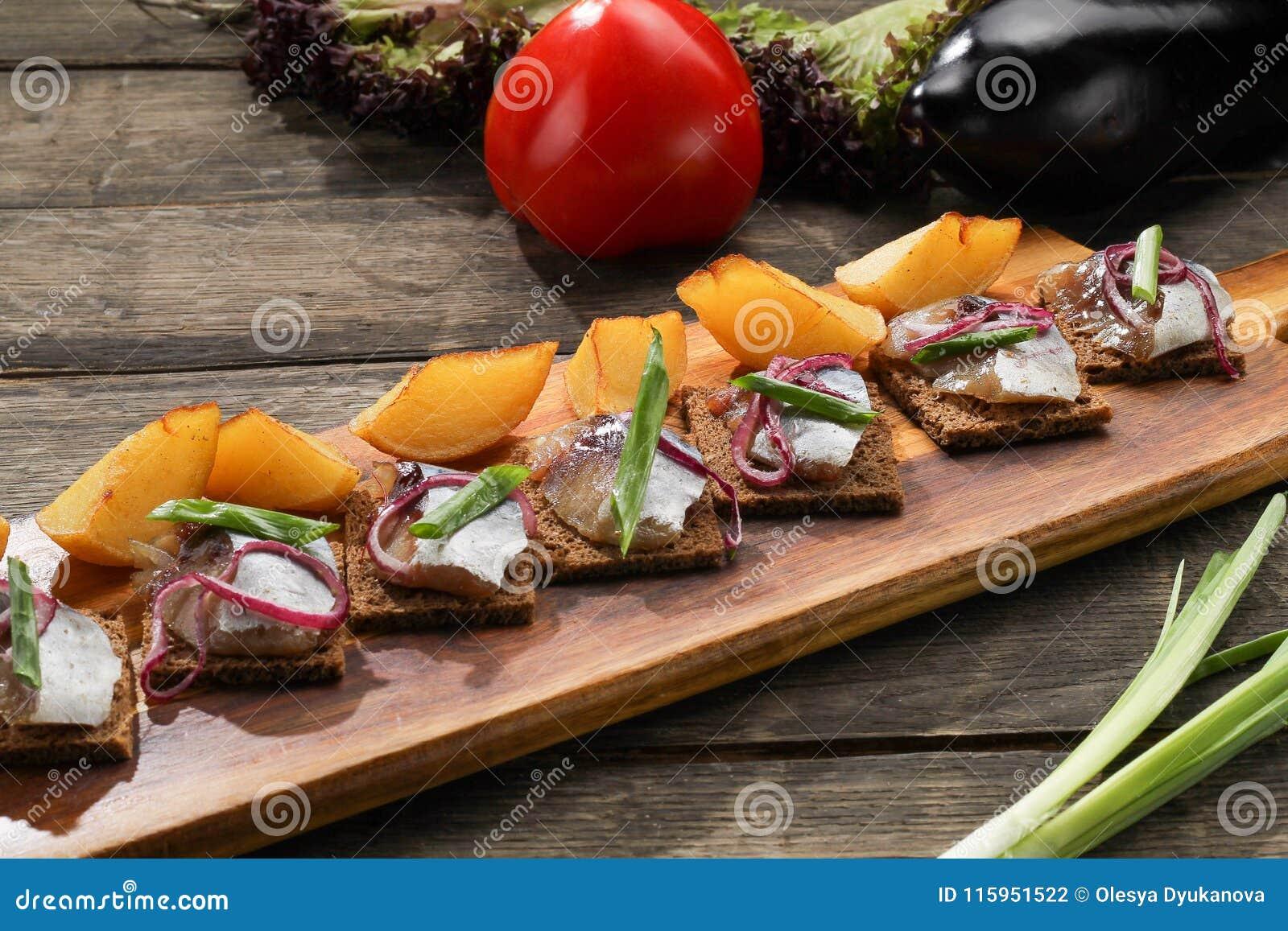 鲱鱼用被烘烤的土豆和葱在盘子在木背景