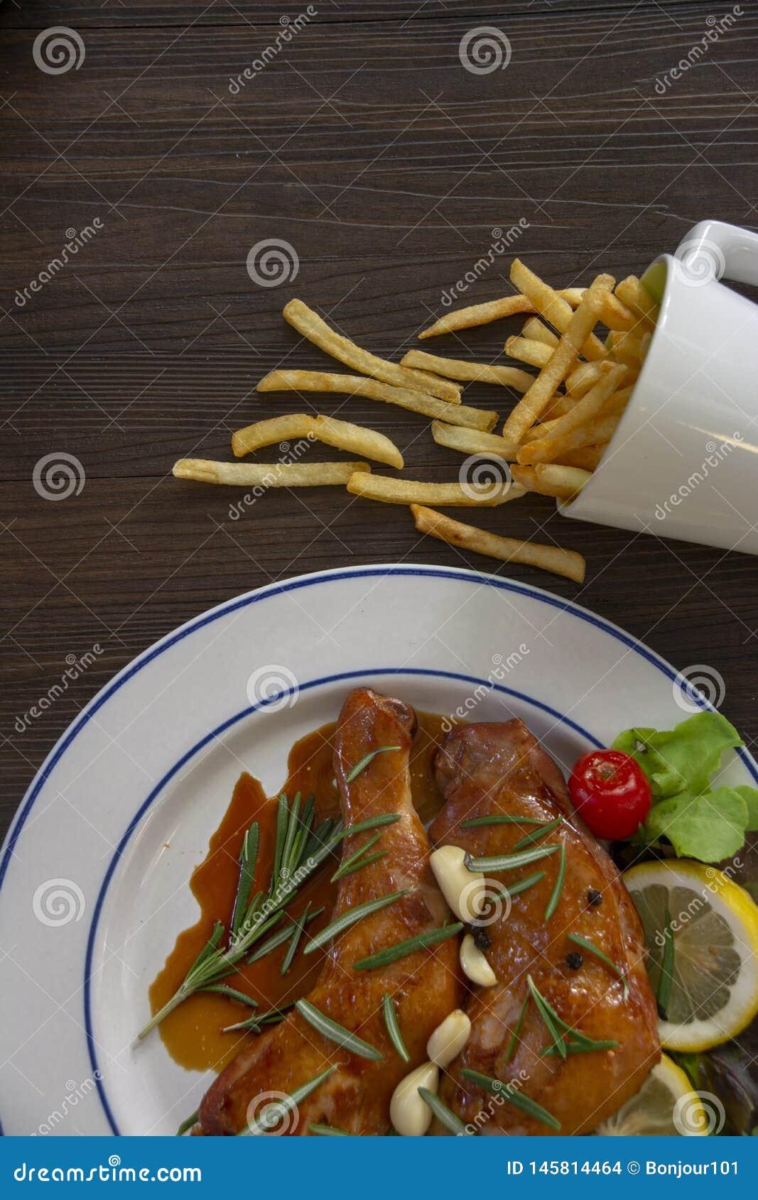 鸡两个片断在一块白色板材被安置,并且调味汁在鸡倒 有与菜的一小菜,