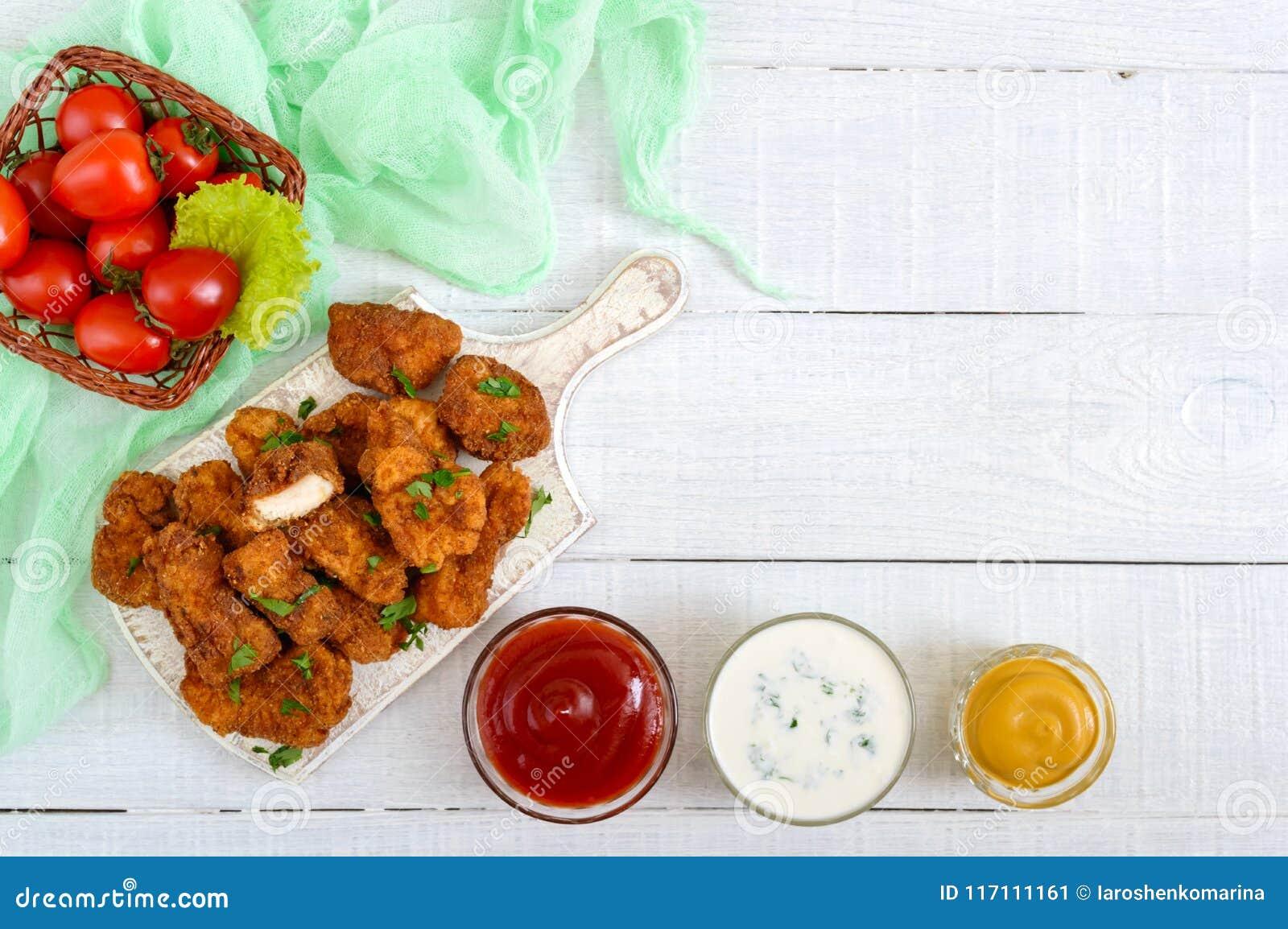 鸡块 油炸酥脆肉片断,在用不同的调味汁的纸在一张白色木桌上